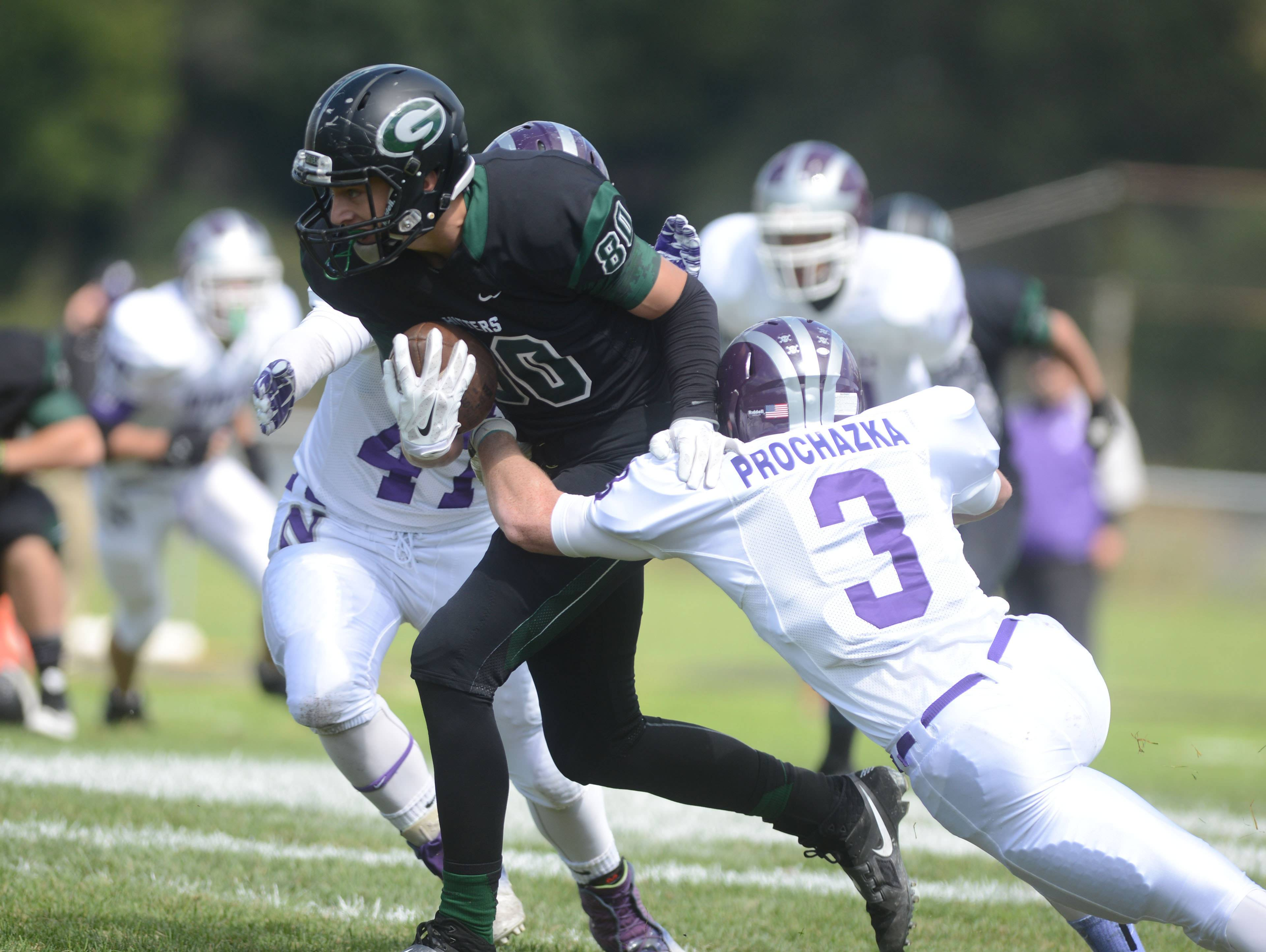 Aidan Gould of Glenbard West moves the ball as Michael Prochazka of Downers Grove North during the Downers Grove North at Glenbard West football game Saturday.