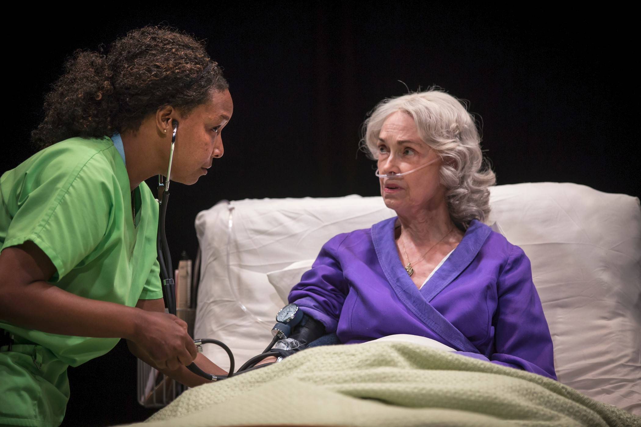 "The ailing Maxine (Deanna Dunagan), right, believes her estranged daughter has arranged for nurse Tina (J. Nicole Brooks) to hasten Maxine's demise in Lucas Hnath's ""Death Tax,"" in its Chicago premiere at Lookingglass Theatre."