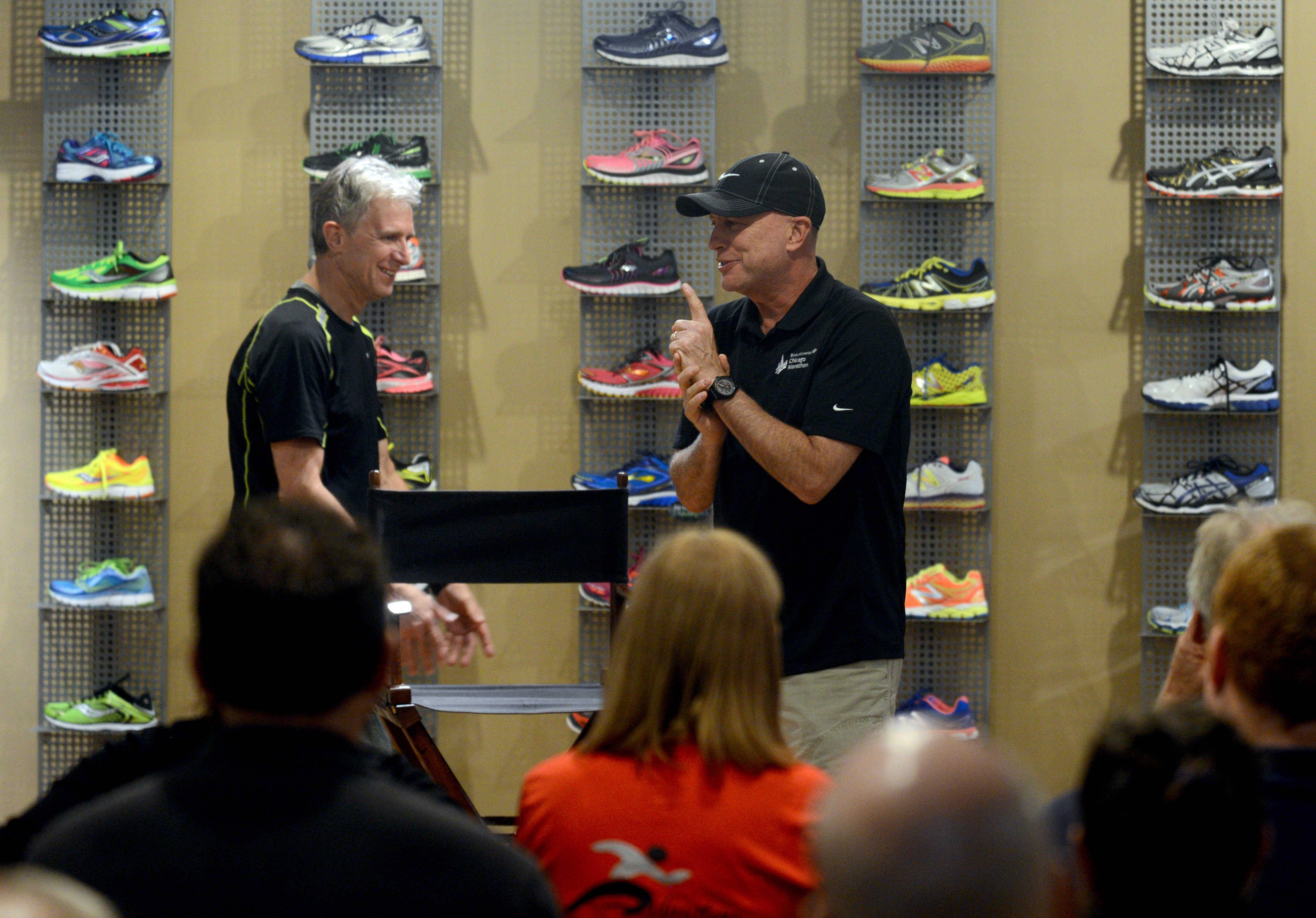 Carey Pinkowski, right, race director for the Chicago Marathon, on Thursday night is introduced by Mark Rouse, left, at the Runners High 'n' Tri shop in downtown Arlington Heights. Rouse is co-owner of the shop.