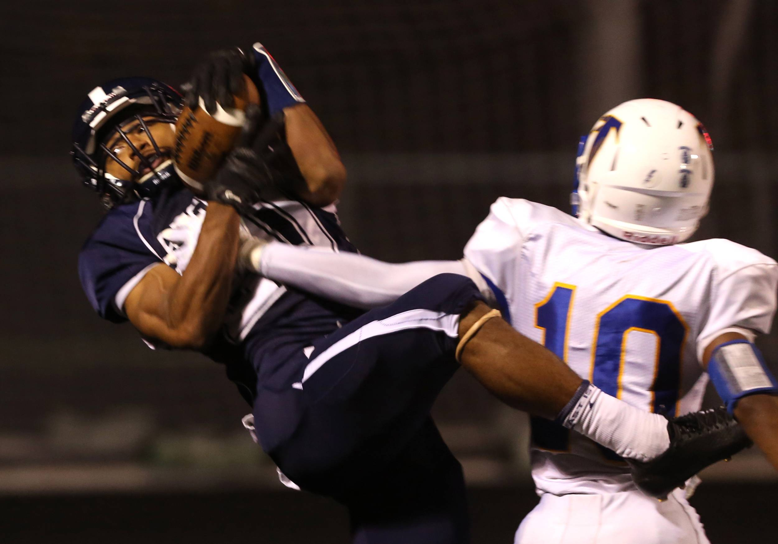 Lake Park's Antonio Shenault, left, grabs a 29-yard touchdown reception under tight coverage from Wheaton North's Ben Moore, right, during first half football action in Roselle.