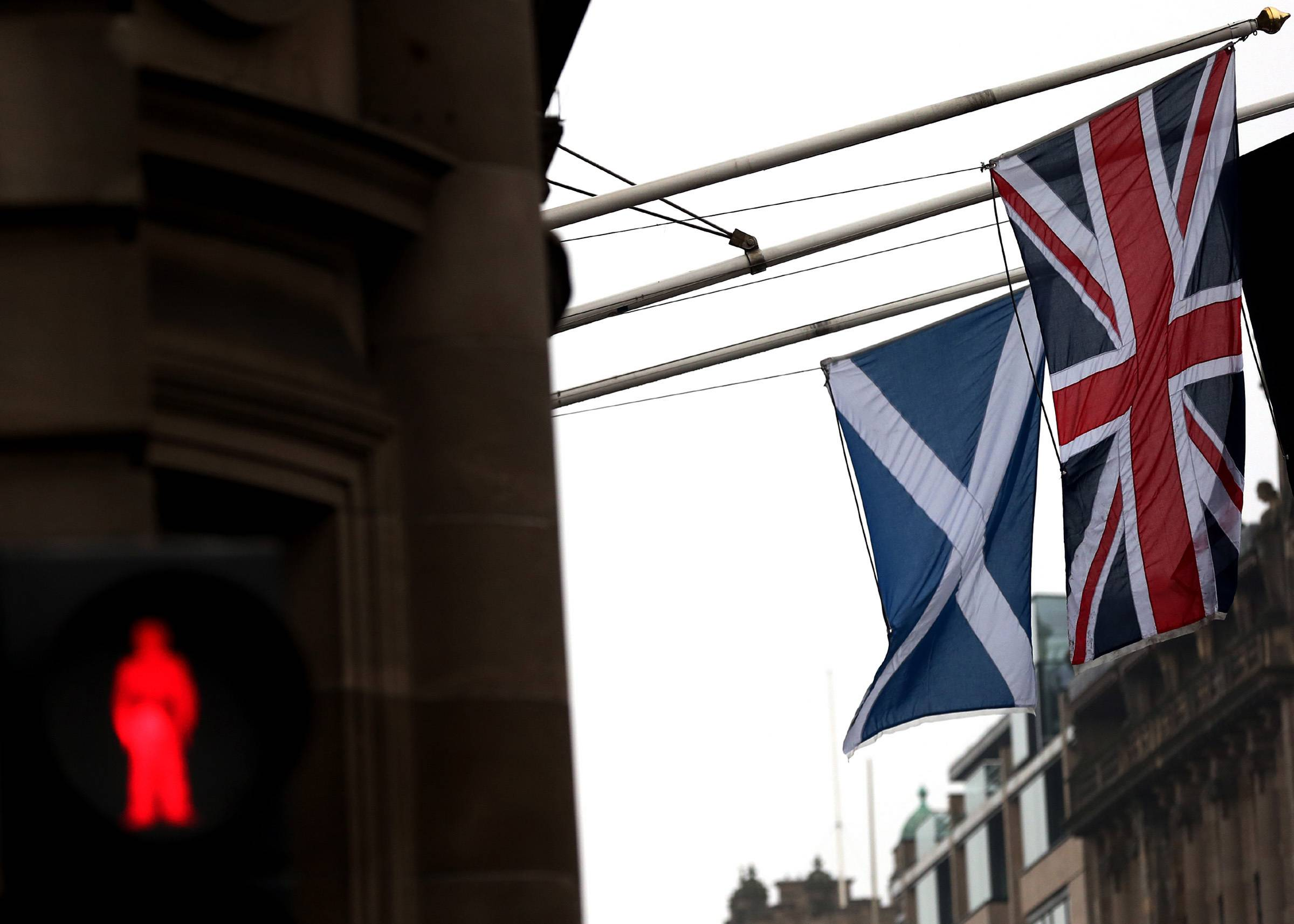 A Saltire and Union Jack flag hang side by side on a building in Edinburgh, Scotland, Friday.