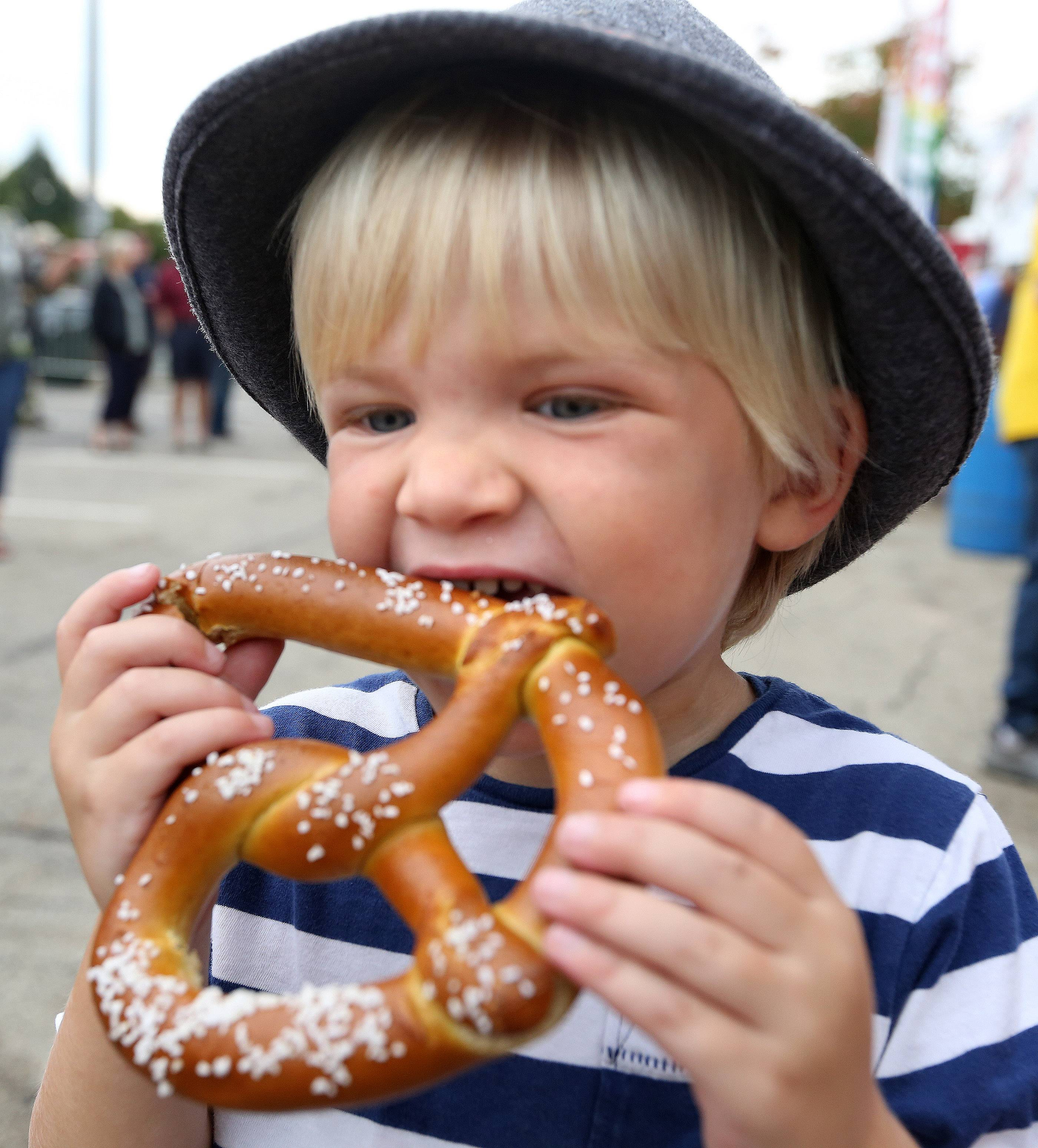 Luke Grybash, 3, of Palatine enjoys a pretzel while wearing his German hat at the 7th annual Rotary of Palatine Oktoberfest on Saturday in downtown, next to the Metra station.