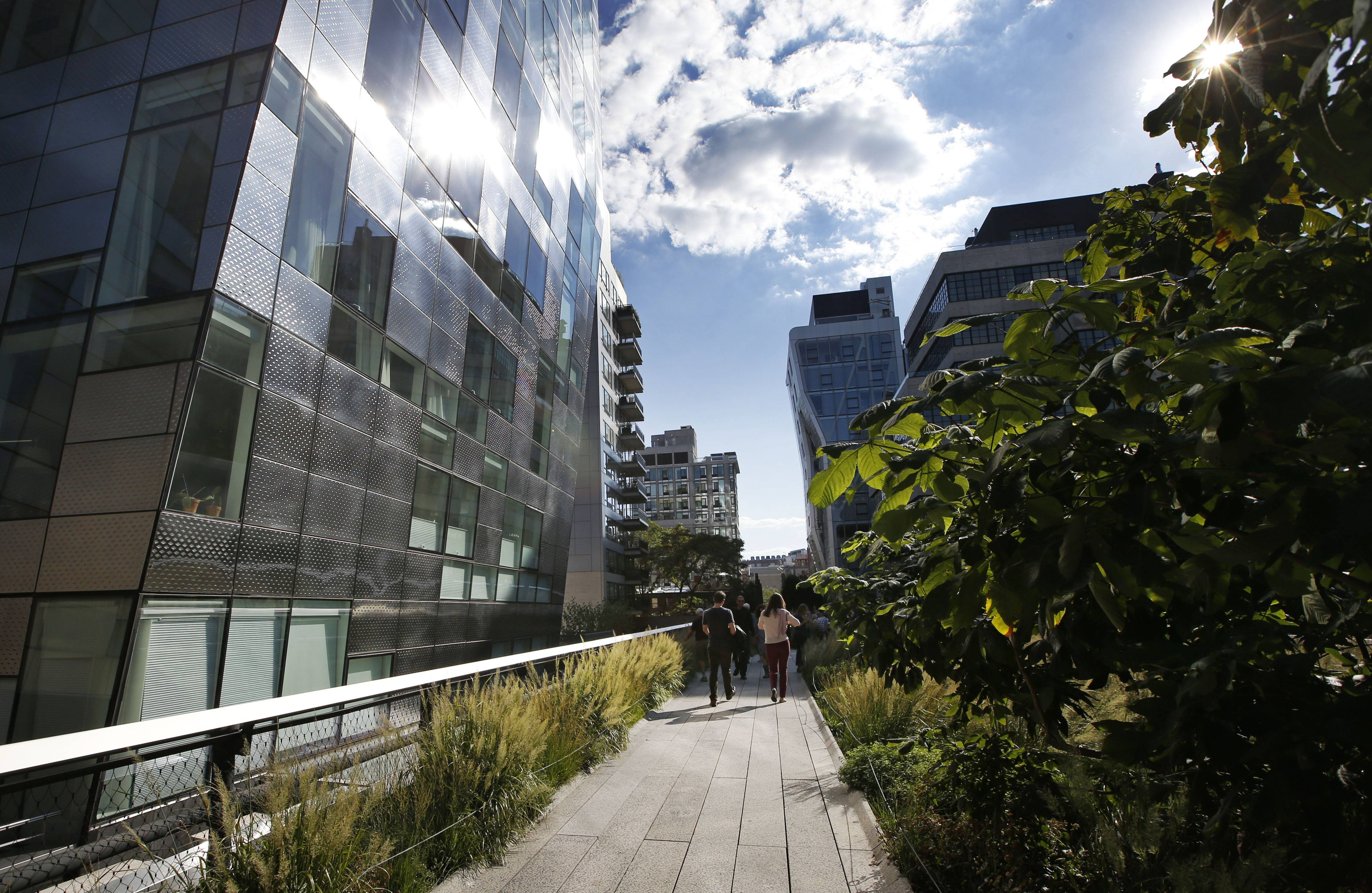 Pedestrians stroll between gleaming luxury apartment buildings Wednesday along the High Line in New York.