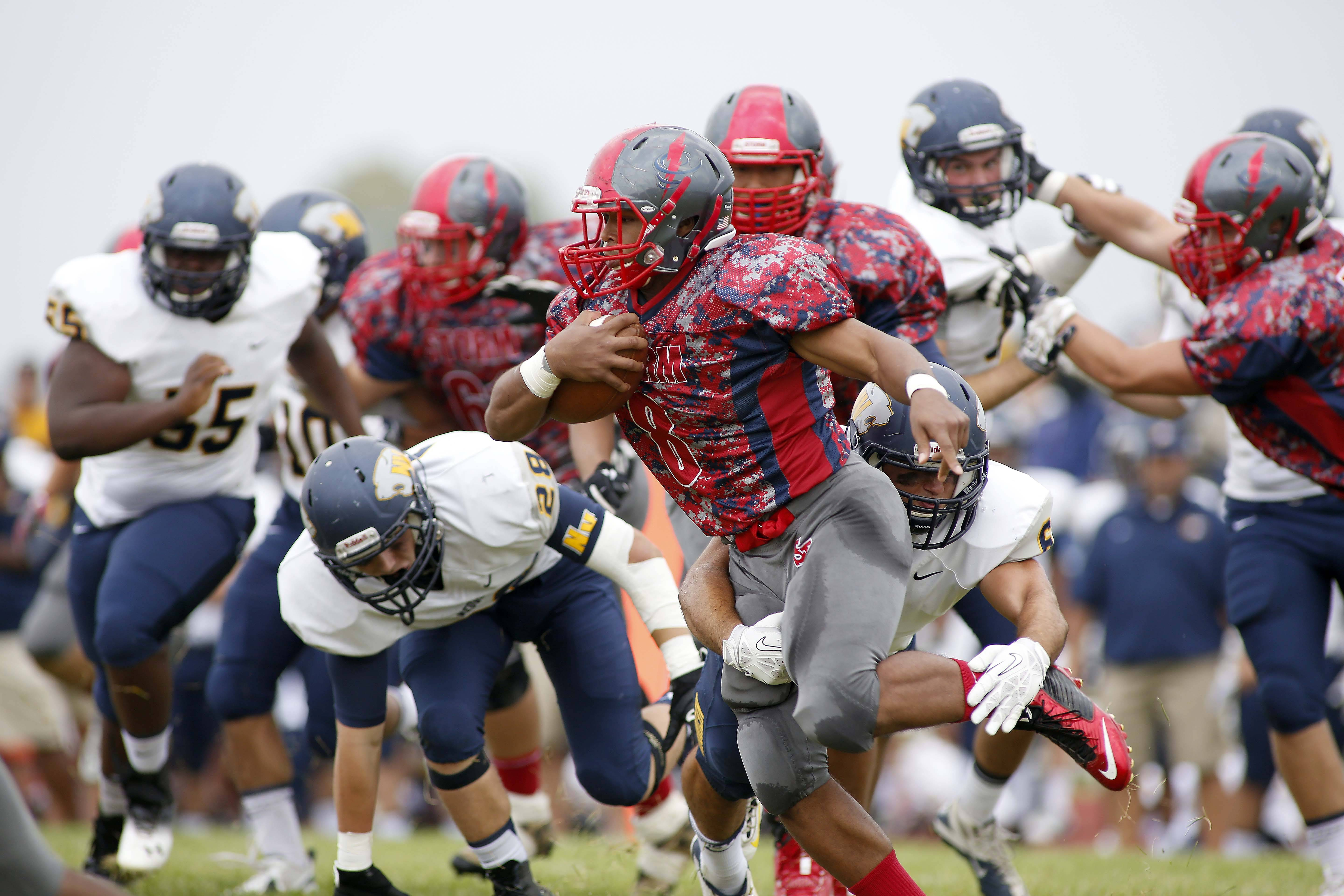 South Elgin running back Kyle Ware (8) tries to avoid a host of Neuqua Valley players during Neuqua Valley football at South Elgin Saturday.