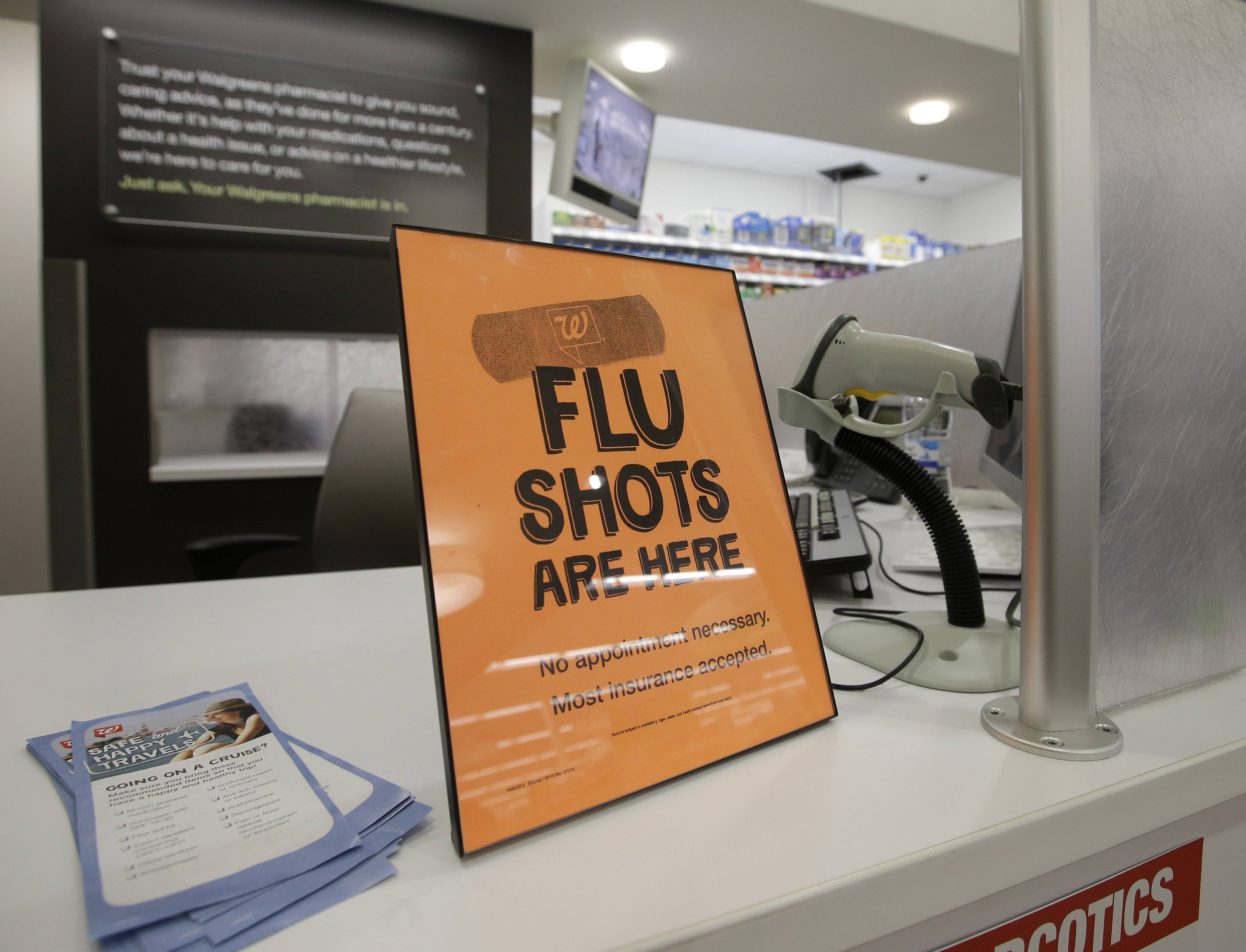 A sign telling customers that they can get a flu shot in a Walgreen store is seen Tuesday in Indianapolis. The nation's biggest drugstores and retailers are grabbing larger chunks of the immunization market, giving customers more convenient options to protect themselves against the flu, pneumonia and more than a dozen other illnesses.
