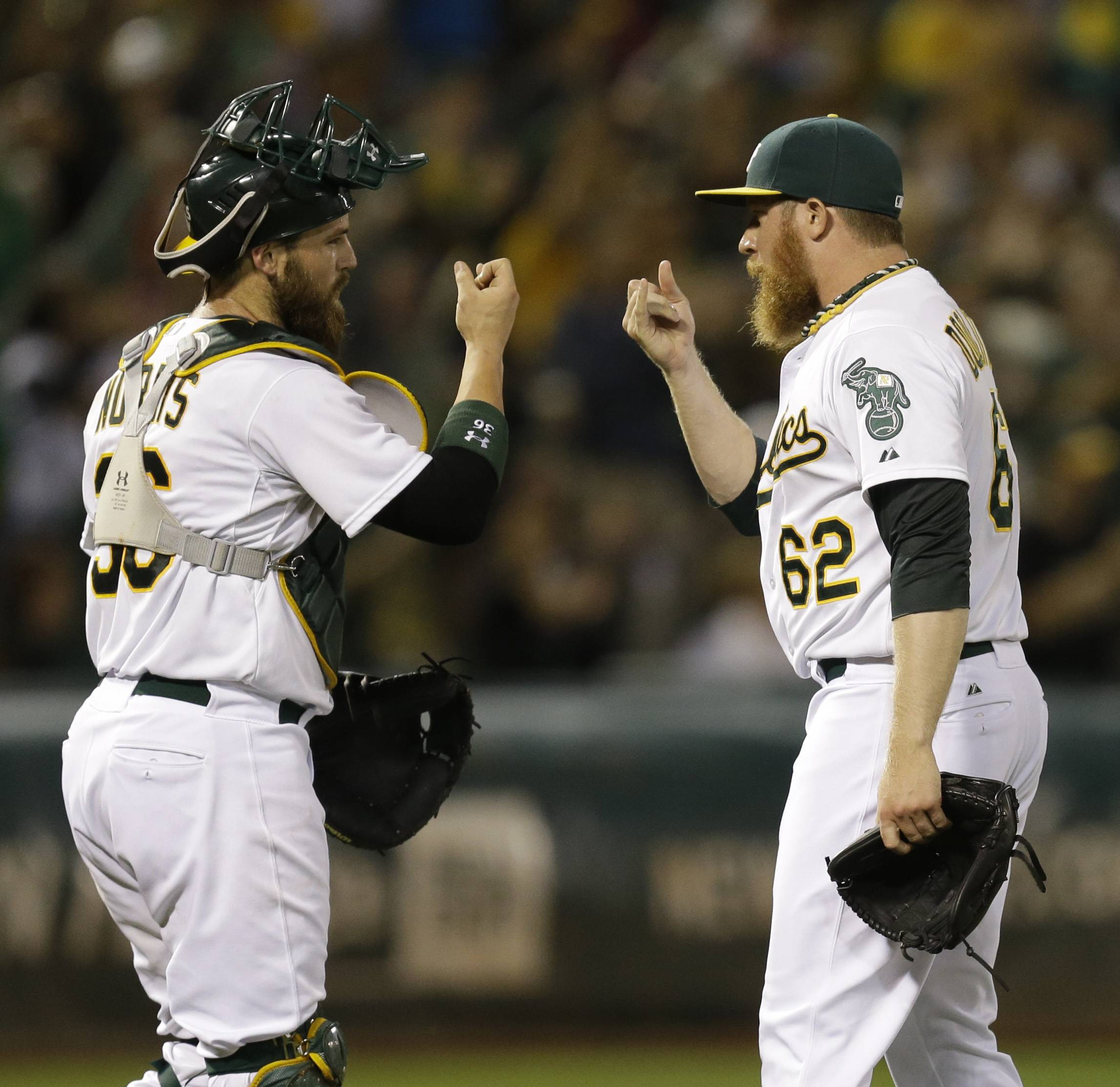 Oakland Athletics' Sean Doolittle (62) and Derek Norris, left, celebrate the A's 3-1 defeat of the Philadelphia Phillies in a baseball game Friday, Sept. 19, 2014, in Oakland, Calif.