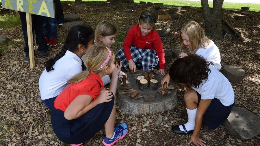 "Holy Family School second-grade girls create an outdoor dinner table, inspired by one of the ""Boxcar Children"" novels."