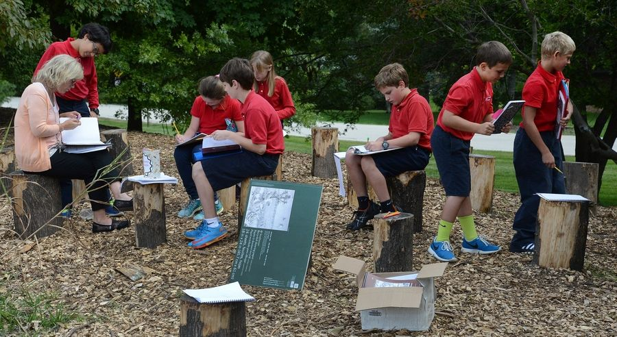 Holy Family School fifth-graders study in their outdoor writing class.