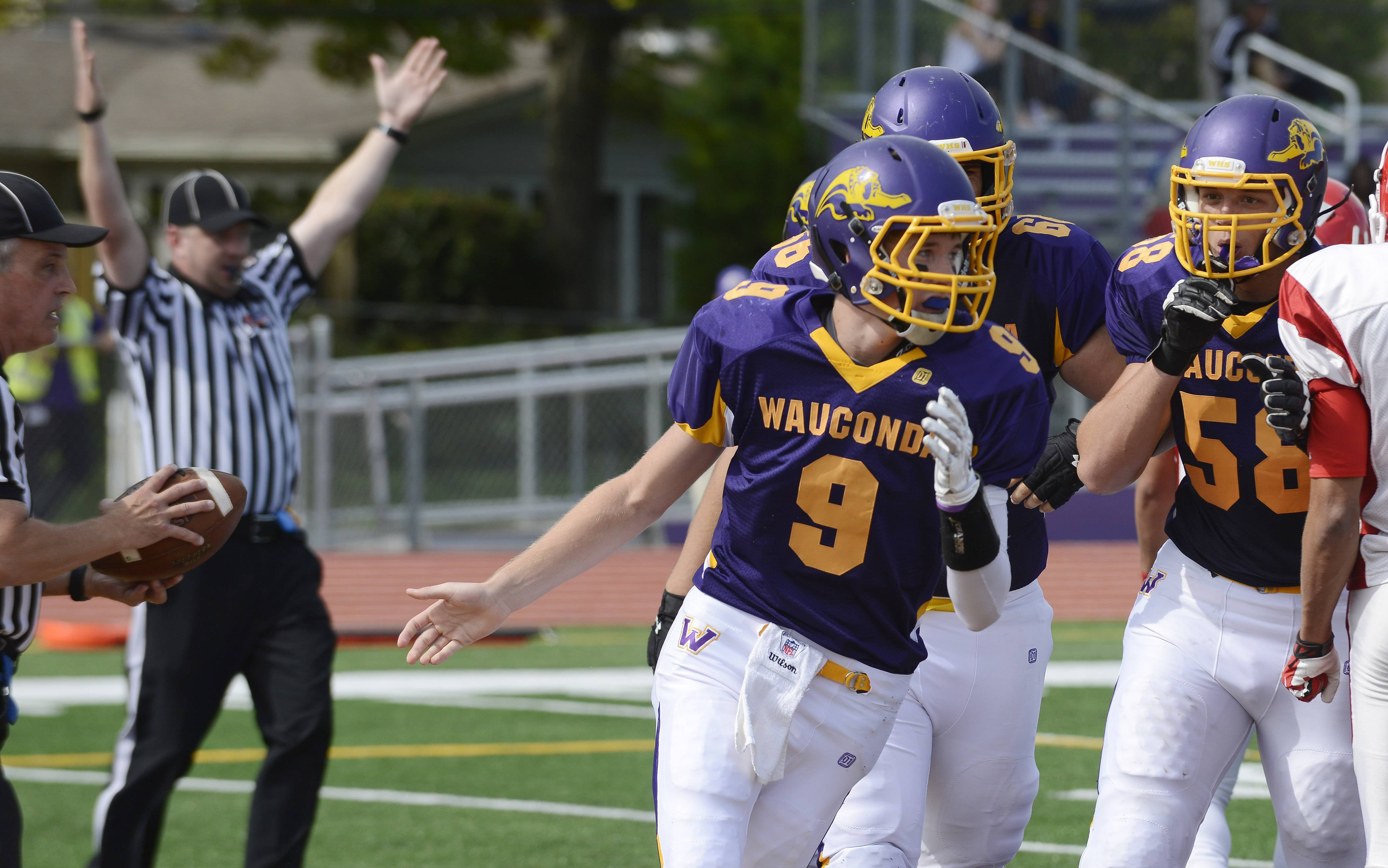 Wauconda quarterback Kevin Malesheski celebrates with his teammates after scoring a first-quarter touchdown during Saturday's game against North Chicago.