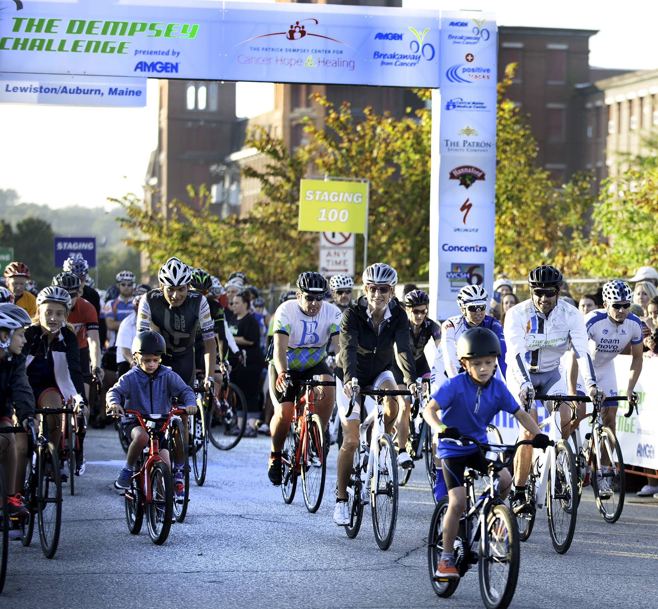 Patrick Dempsey, second from right, is joined by his family, friends, professional riders, supporters and community members as the first wave of bicyclists take to the streets in Lewiston, Maine, at the start of the 2014 Dempsey Challenge bike ride. The challenge is a fundraiser for cancer research and care that is in its sixth year.
