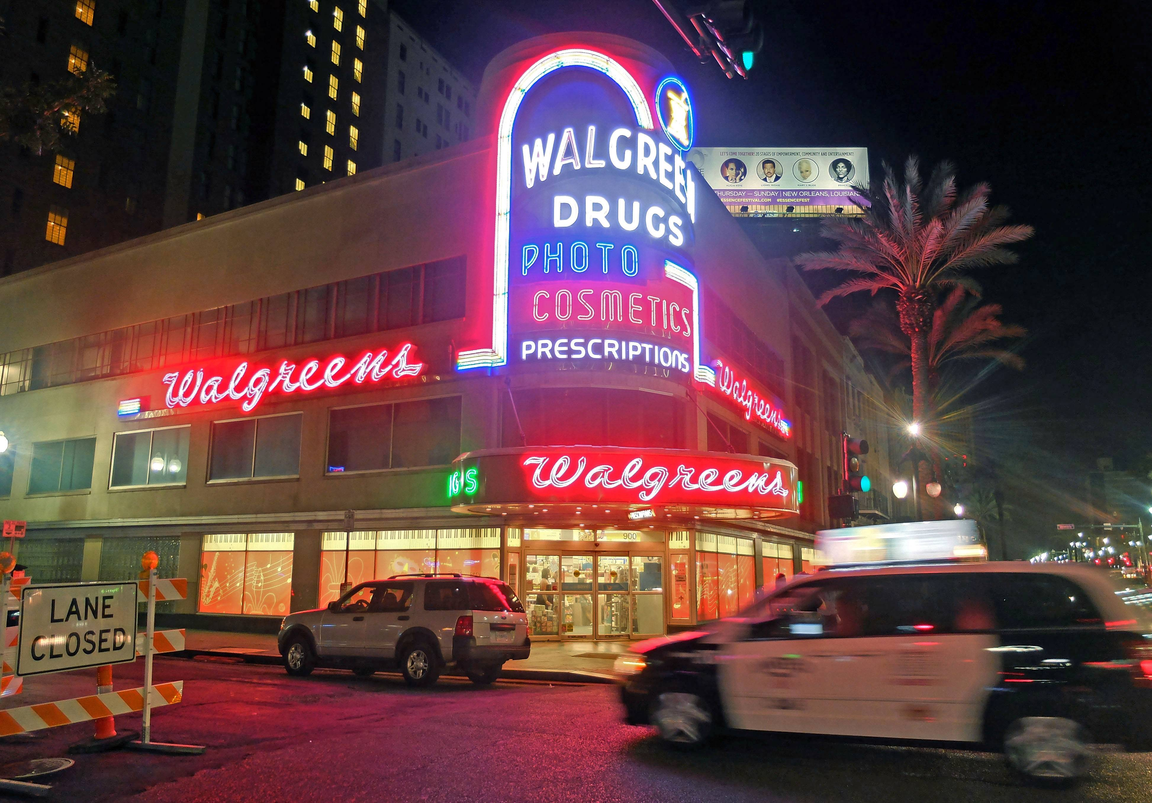 A taxi speeds by a neon-lit Walgreens in the French Quarter of New Orleans. Walgreen booked a $239 million loss in its fiscal fourth quarter after swallowing a huge accounting charge from its Alliance Boots acquisition, but the drugstore chain's results still met Wall Street expectations.