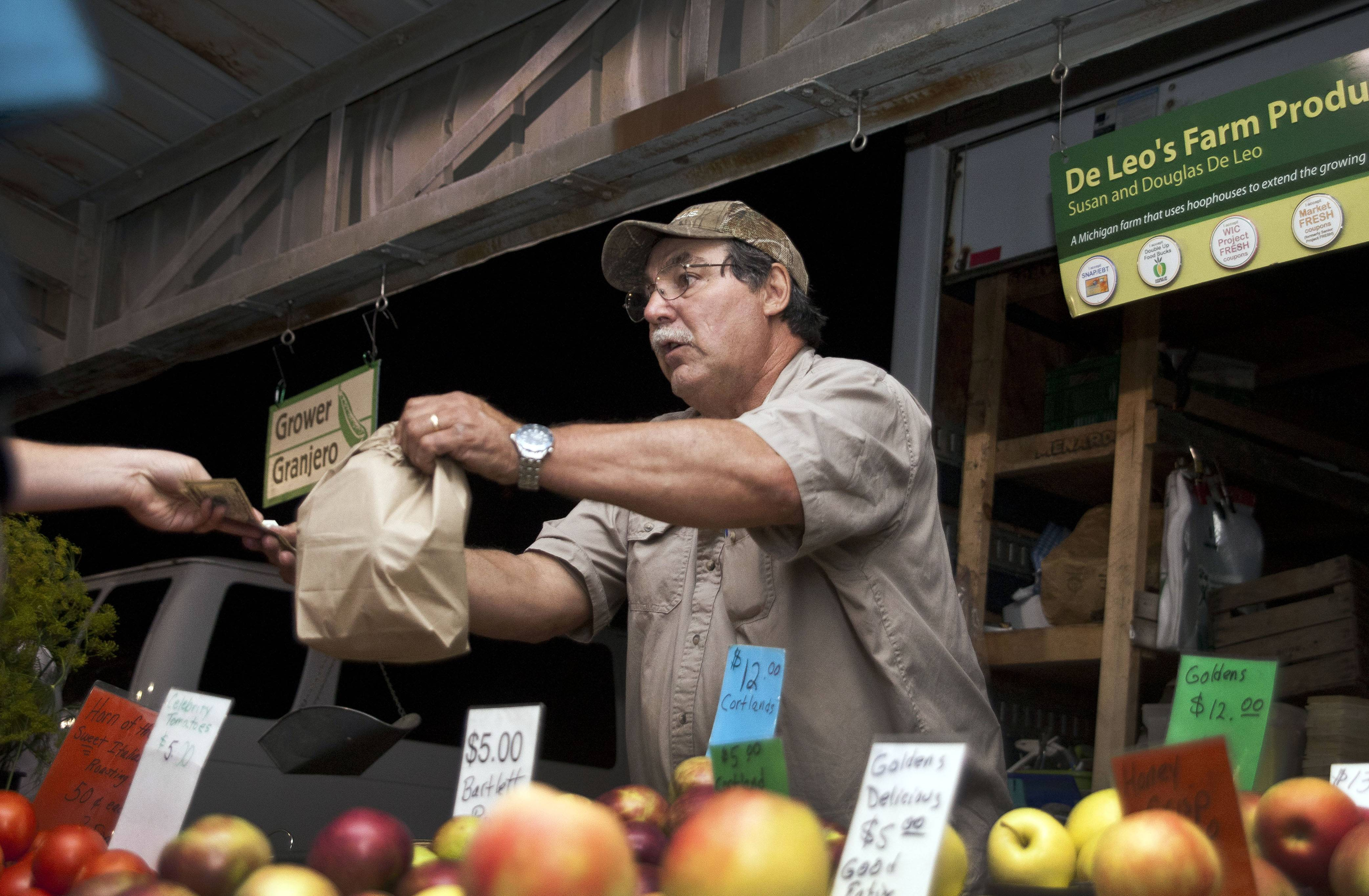 Douglas De Leo hands customers a bag of produce at the Kalamazoo Farmers Market in Kalamazoo, Mich. U.S. consumer confidence dropped in September after hitting the highest level in nearly seven years in August.