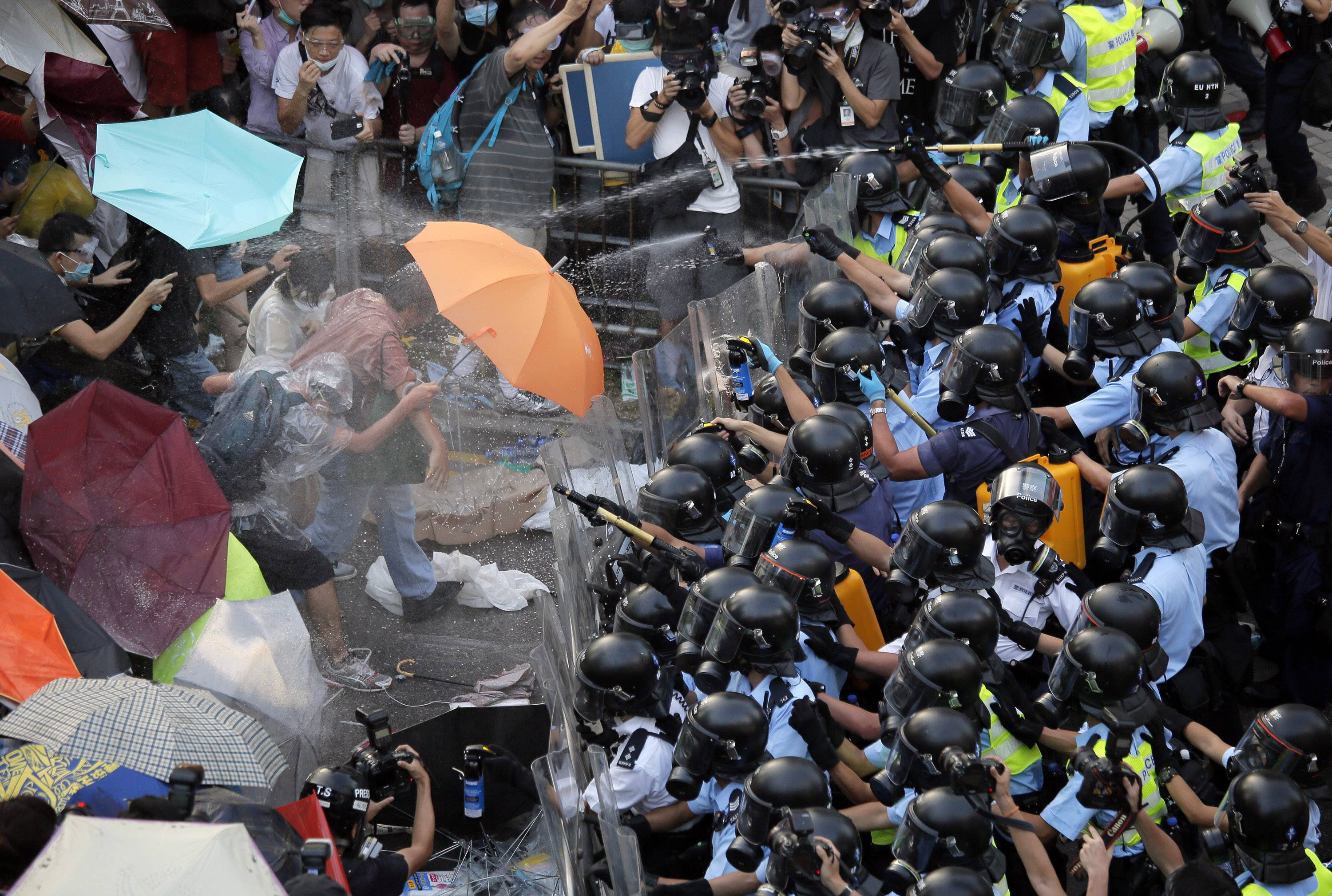 Riot police use pepper spray against protesters after thousands of people block a main road to the financial central district outside the government headquarters in Hong Kong on Sunday. Ubiquitous images in Hong Kong media with masses of unarmed students fending off pepper spray with umbrellas could not contrast more starkly with mainland China's virtual blackout of news about the territory's pro-democracy protests.