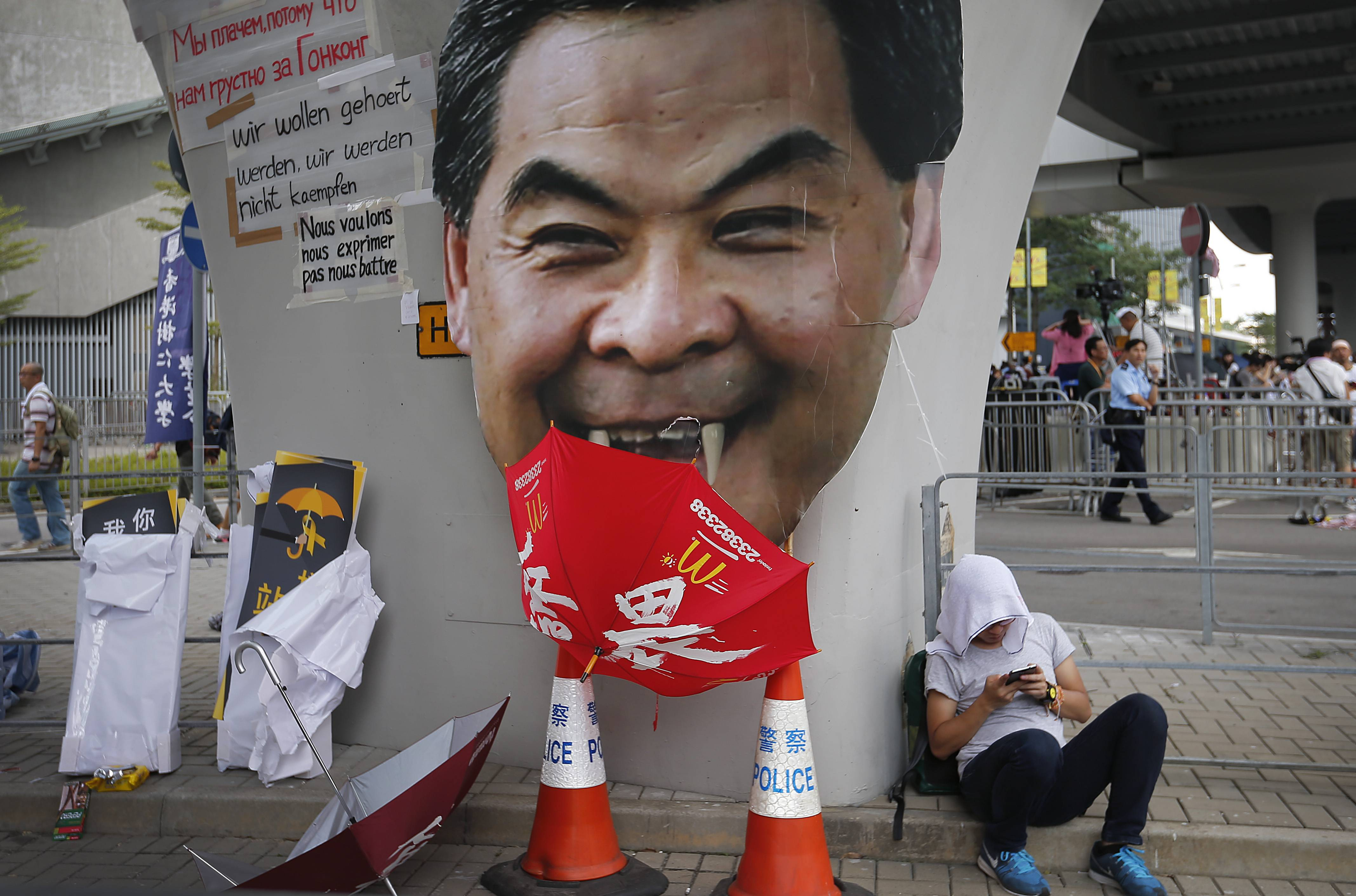A student protester rests next to a defaced cutout of Hong Kong's Chief Executive Leung Chun-ying at one of their protest sites around the government headquarters, Tuesday, Sept. 30, 2014, in Hong Kong. Pro-democracy protesters in Hong Kong set a Wednesday deadline for the city's unpopular Chief Executive Leung Chun-ying to meet their demands for genuine democracy and for him to step down as leader of Hong Kong, after spending another night blocking streets in an unprecedented show of civil disobedience.