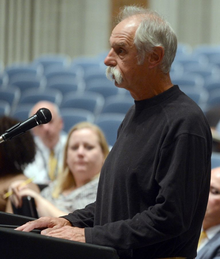 Elgin resident Gary Swick speaks during Tuesday night's public hearing about a charter school proposal before the Illinois Charter School Commission at Larkin High School in Elgin.