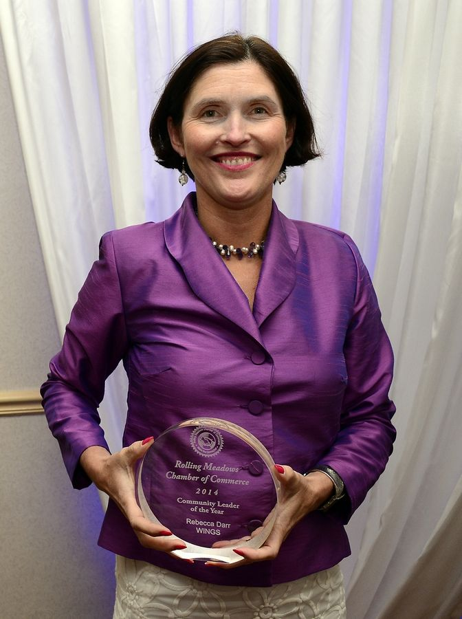 Rebecca Darr of WINGS, as she picks up the Community Leader of the Year award at the Rolling Meadows Chamber of Commerce annual recognition dinner in late May.