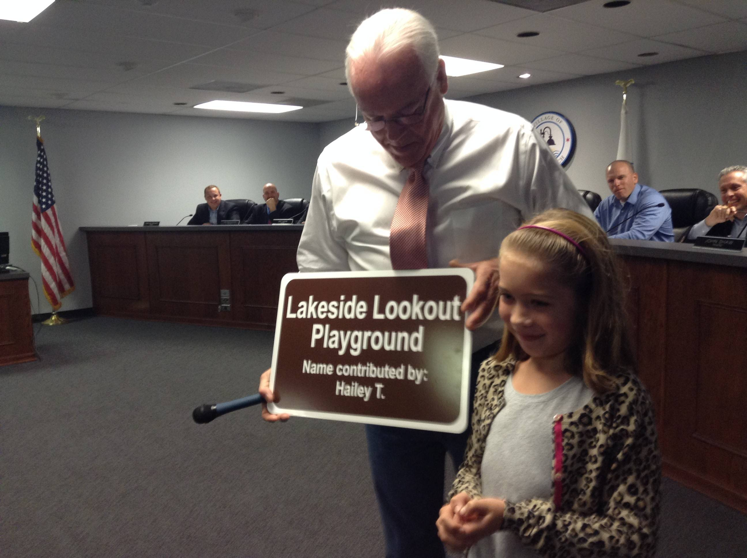 Lake Zurich Mayor Thomas Poynton accepts a sign designating Lakeside Lookout Playground at Paulus Park from 8-year-old Hailey Thorp. Hailey came up with the name and her family donated the sign to the village this week.
