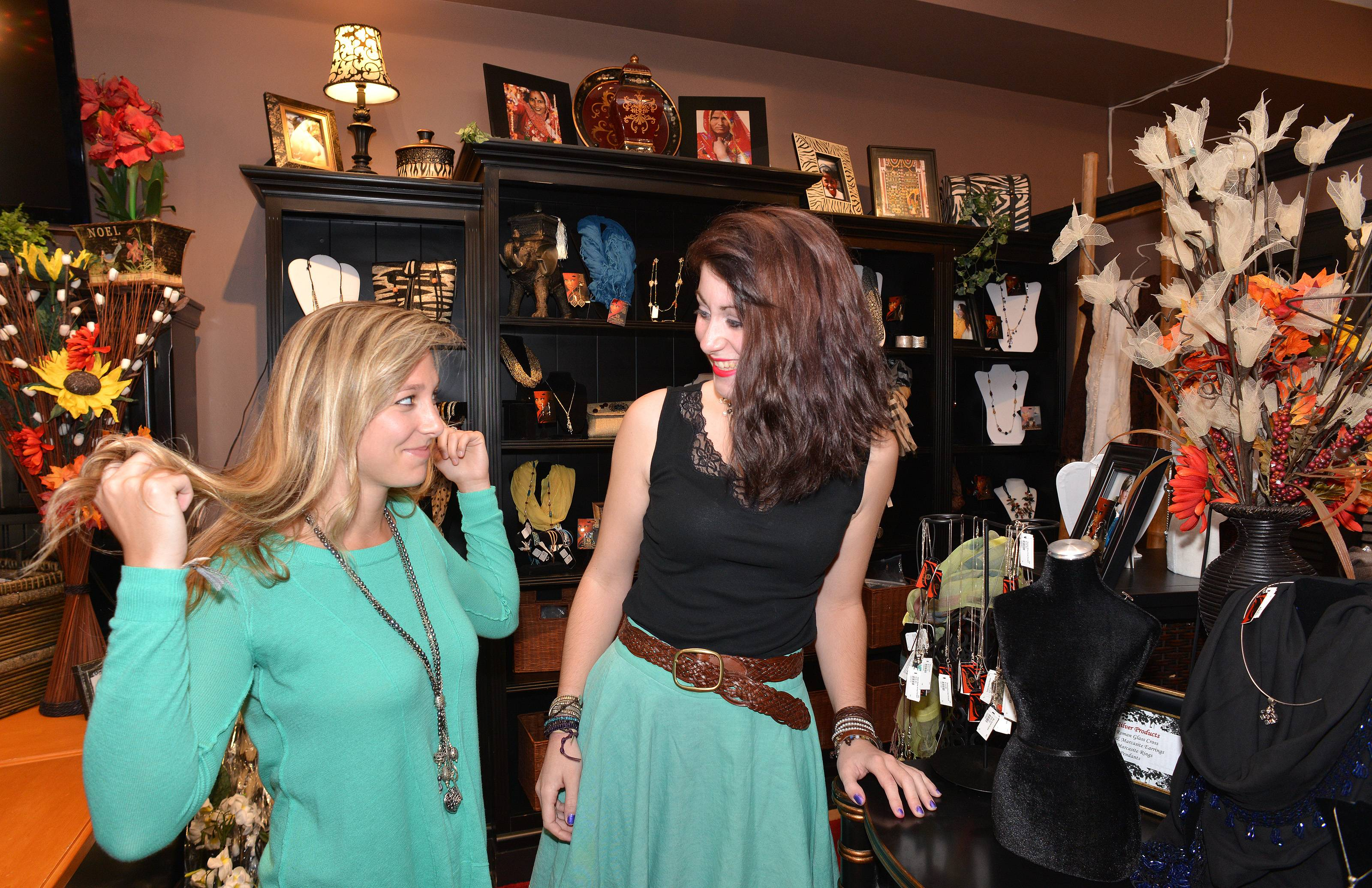At the WAR Chest Boutique in Naperville, Jessie Dattalo of Wheaton, left, tries on a necklace made by a human trafficking victim in a safe house in the U.S. while Meggie Zayas of Lombard watches.