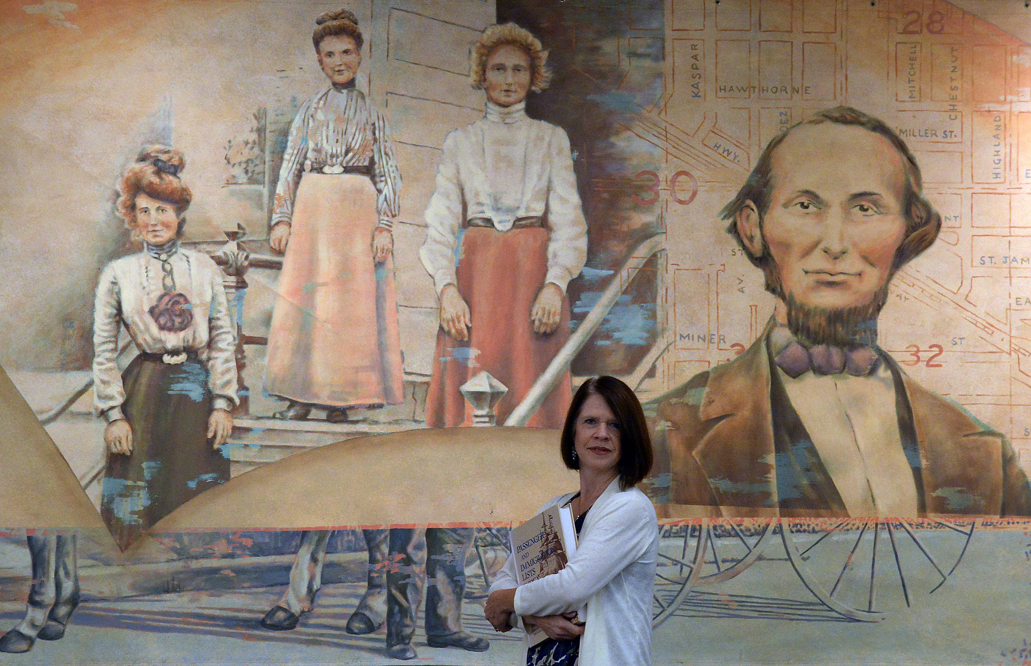 Teresa Steinkamp McMillin, a certified genealogist who specializes in German ancestry, as well as Chicago and Midwestern searches for clients across the country, stands in front of a mural representing the past of Arlington Heights at the Arlington Heights Memorial Library.