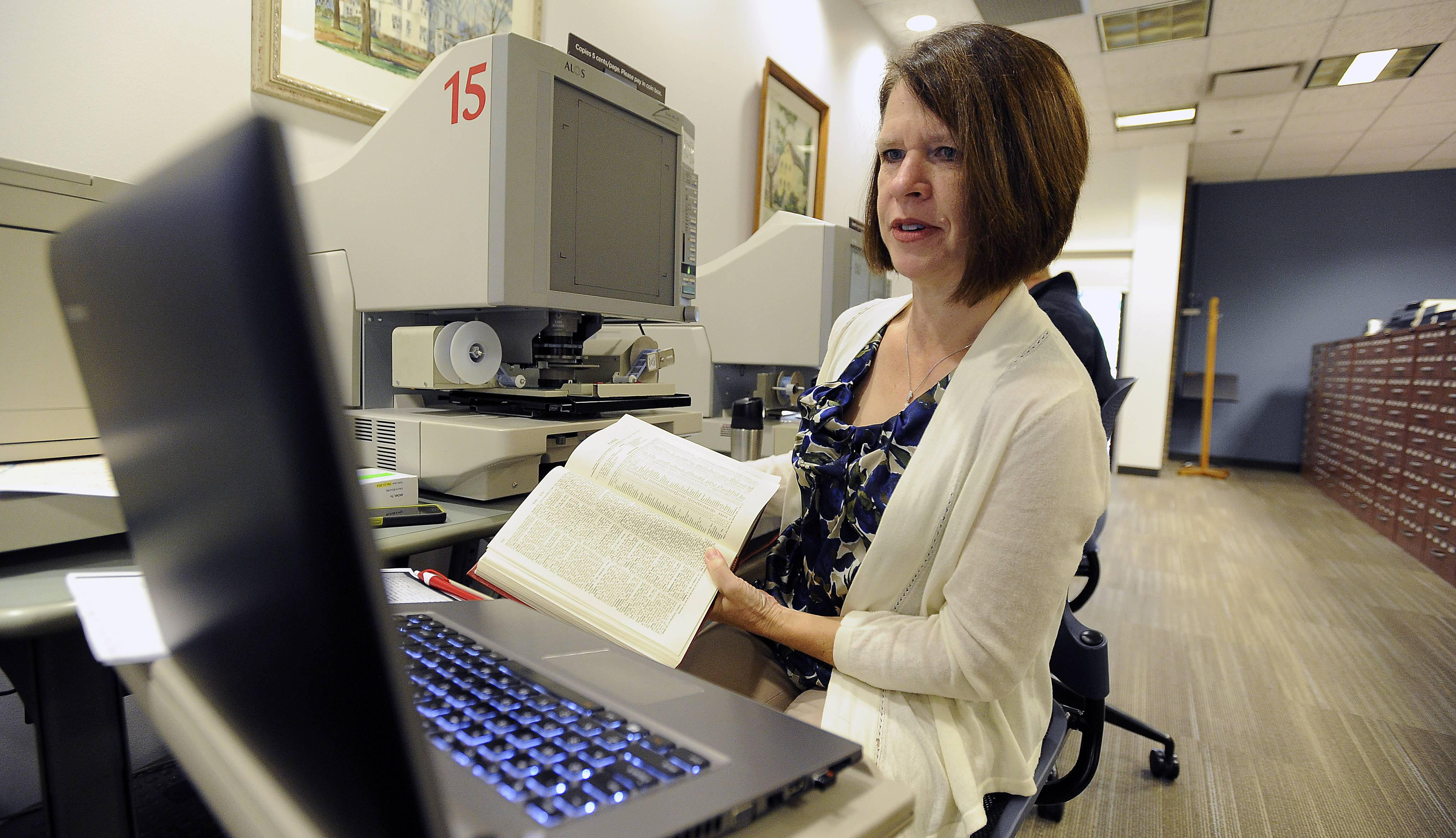 "Teresa Steinkamp McMillin, shown doing research at Arlington Heights Memorial Library genealogy department, is a popular speaker and author of ""Guide to Hanover Military Records, 1514-1866, on Microfilm at the Family History Library."""