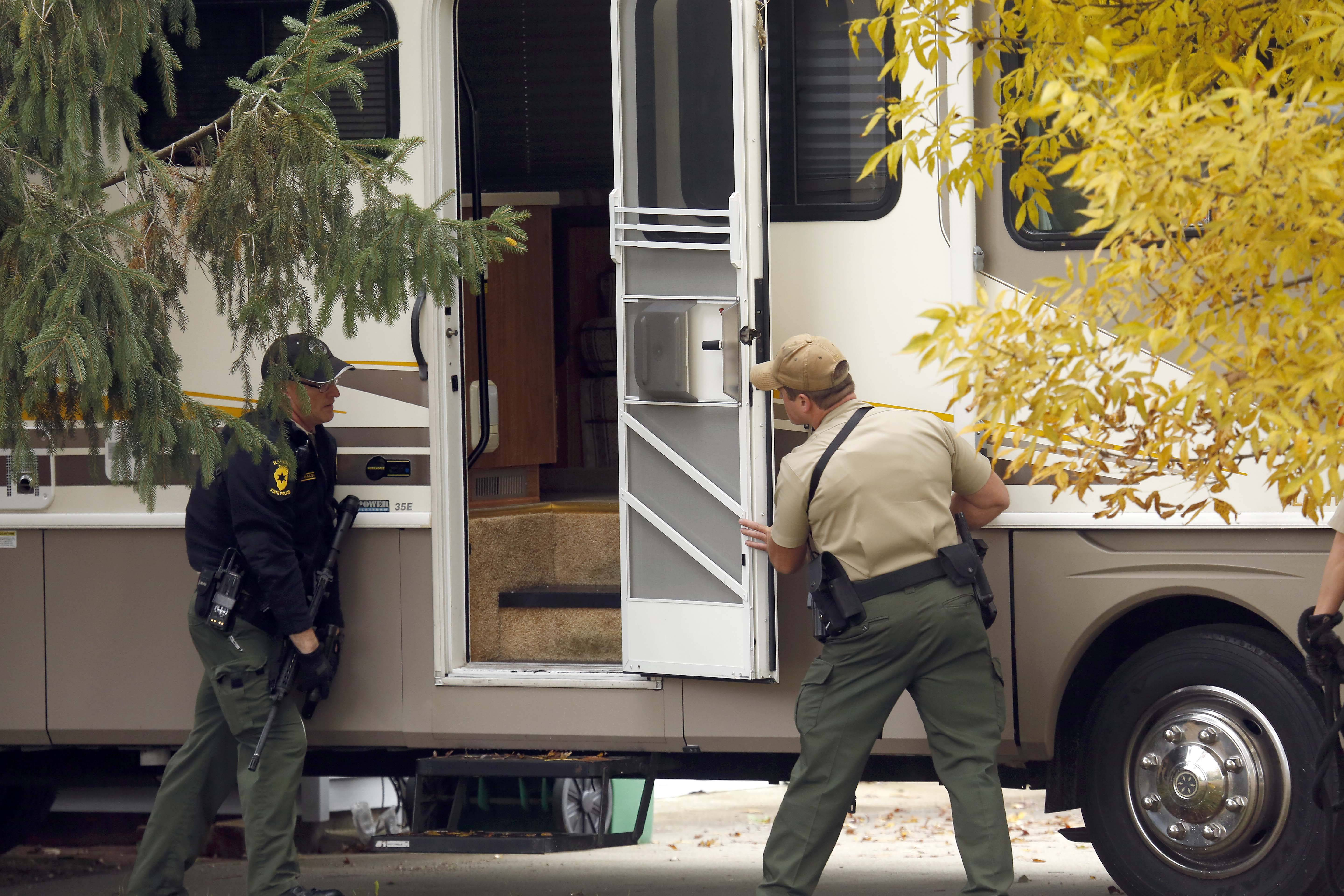 Illinois State Police officers search a recreational vehicle for Scott B. Peters Thursday in Holiday Hills.