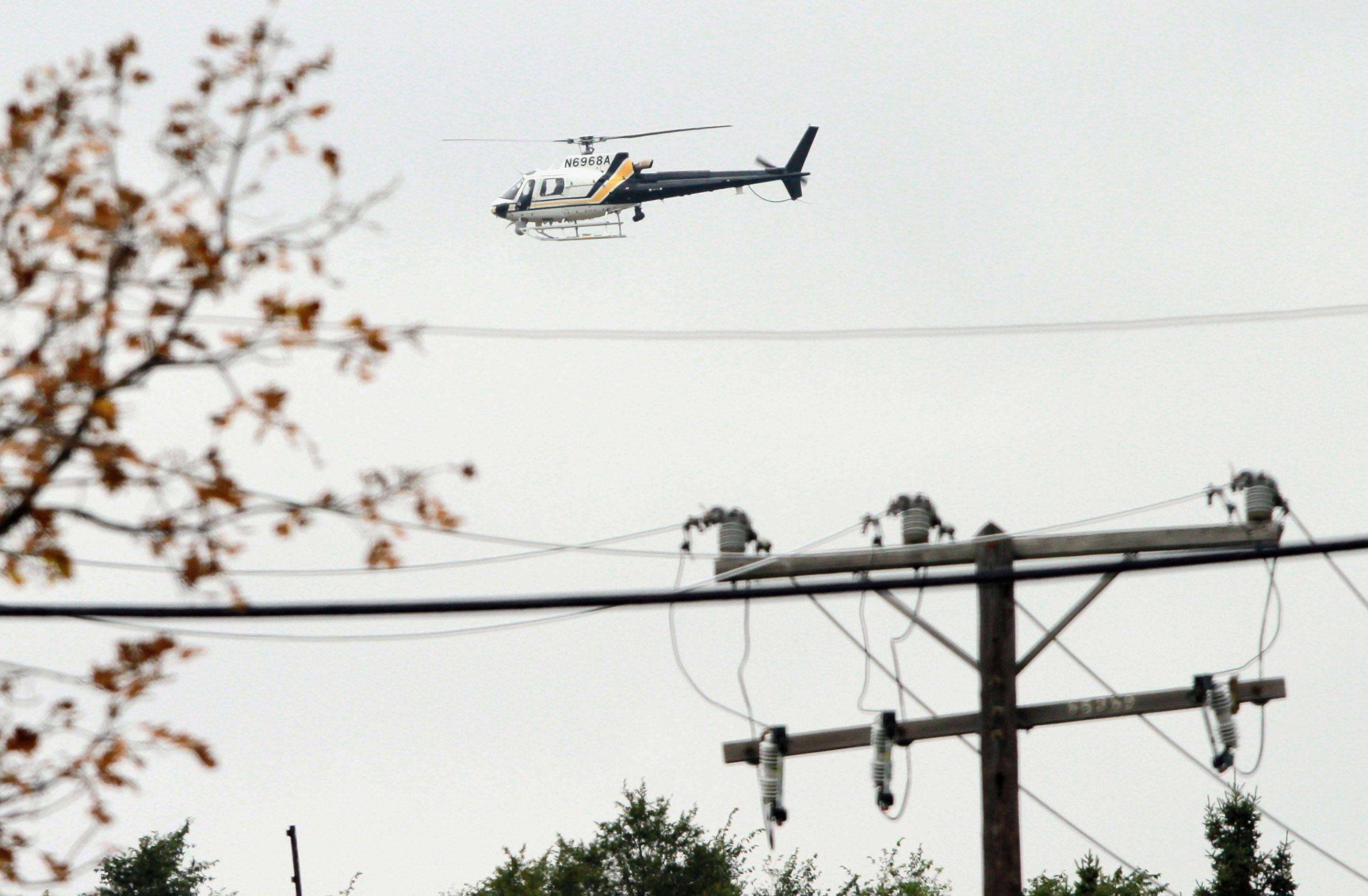 A helicopter searches a subdivision in Hollywood Hills Thursday.