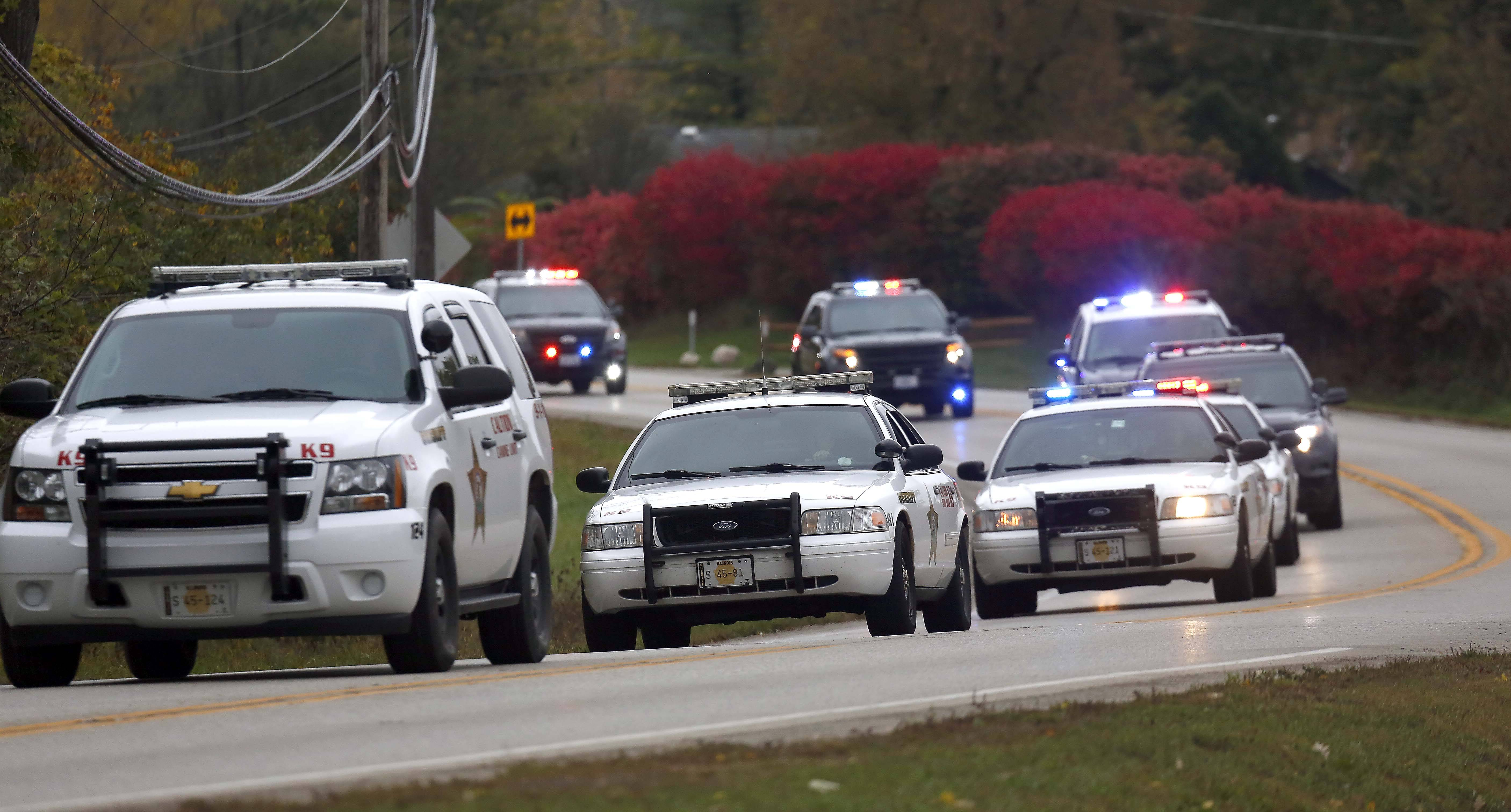 Police K-9 units head into the Holiday Hills neighborhood Thursday to search for Scott B. Peters.
