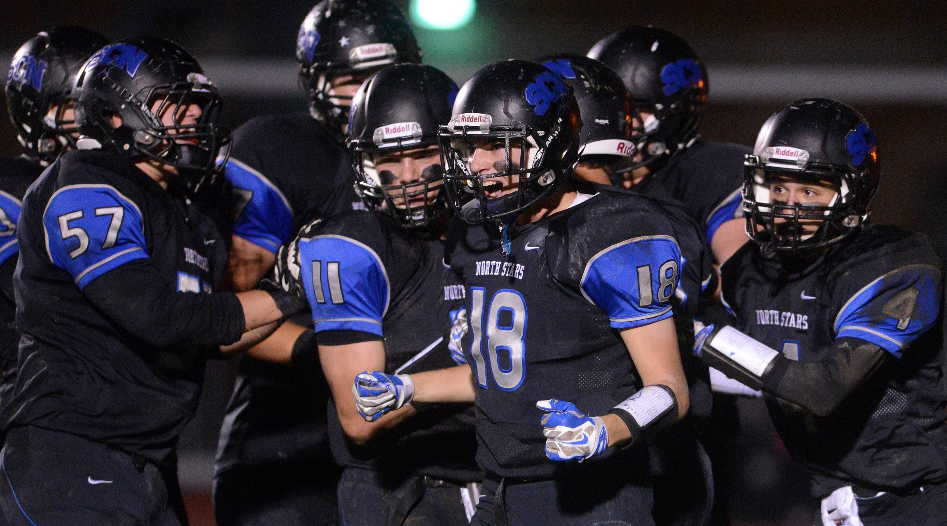 St. Charles North's Blake Kastein and his teammates celebrate one of the North Stars four first-half touchdowns against St. Charles East .