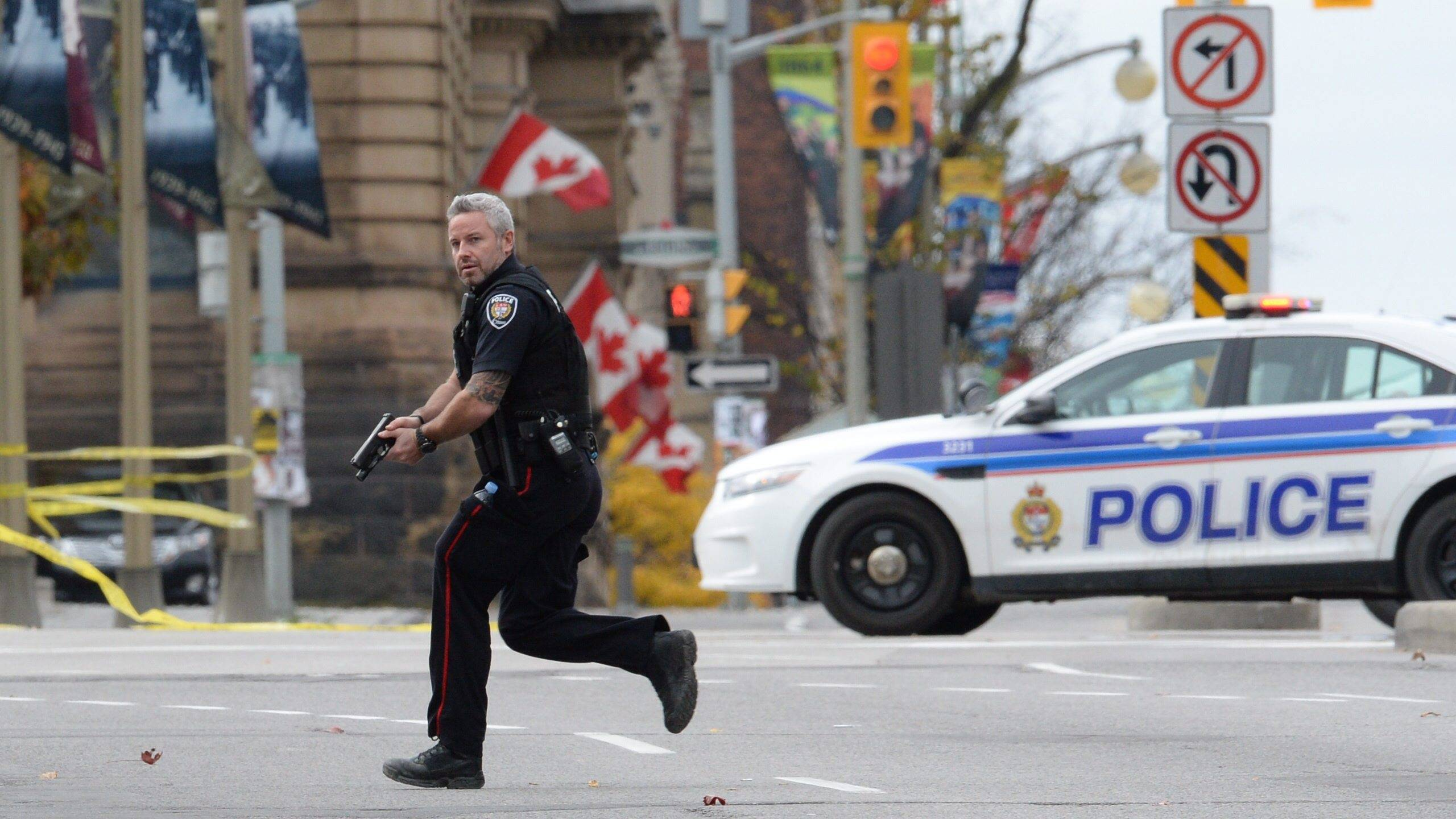 An Ottawa police officer runs with his weapon drawn outside Parliament Hill in Ottawa on Wednesday Oct. 22, 2014.
