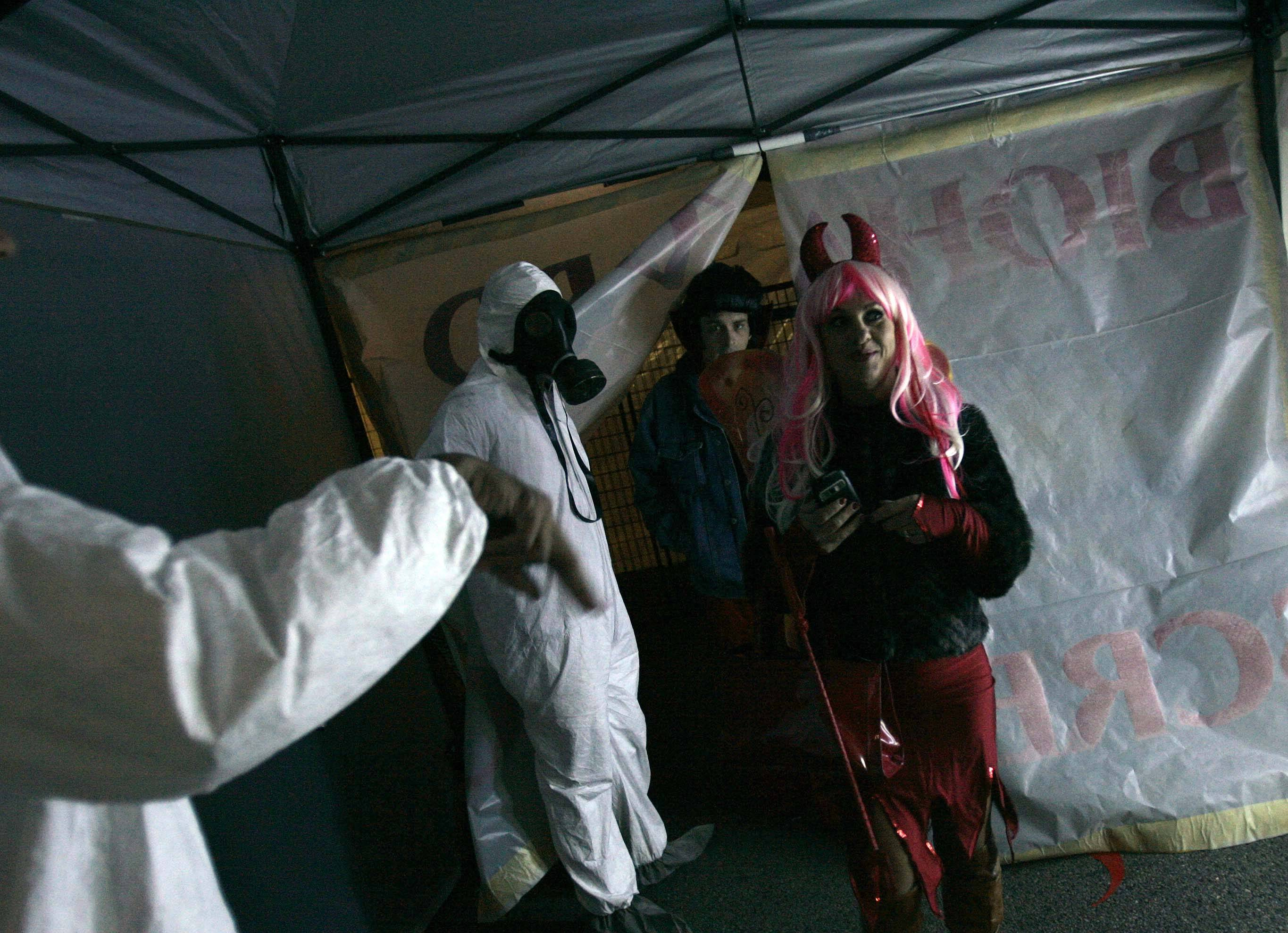 "Donna and Rob Wilhelm of Algonquin make their way through the decontamination station as they enter Elgin's annual Halloween party, ""Nightmare on Chicago Street."""