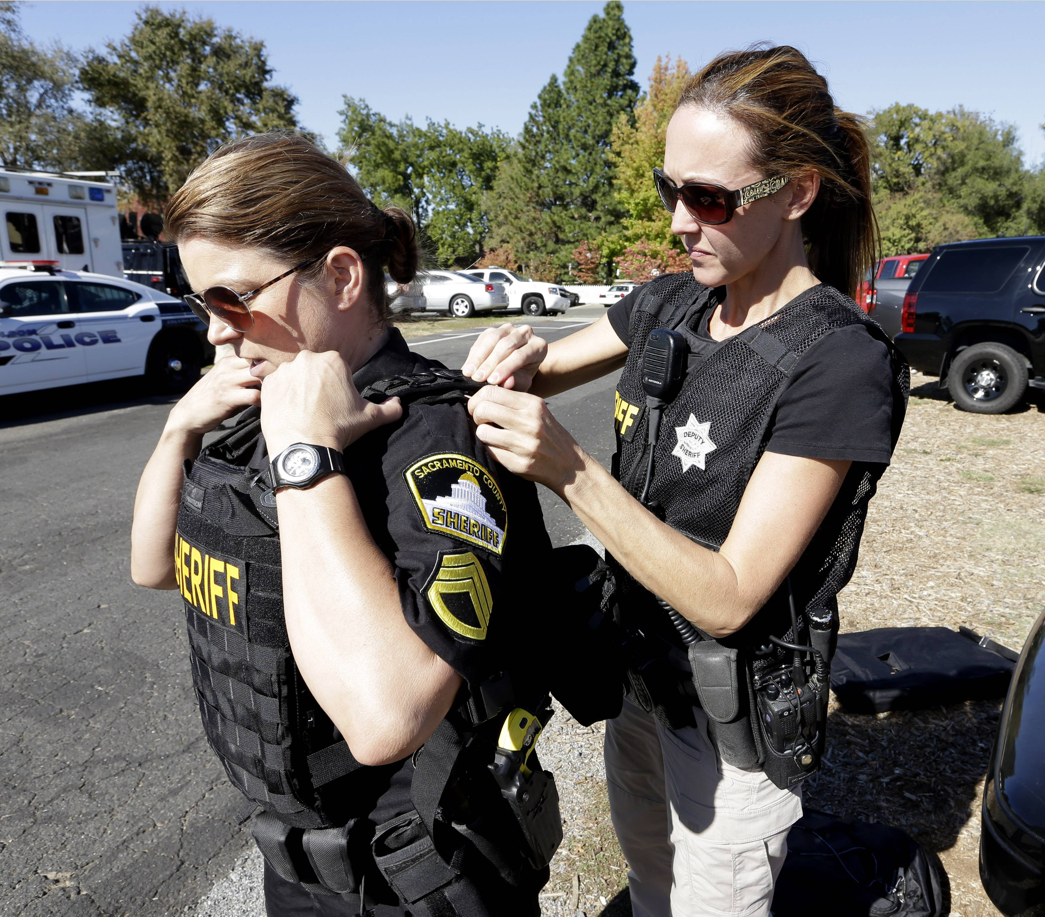 Sacramento County Sheriff's Detective Christie Lynn, right, tightens the protective vest of deputy Sgt. Donna Cox as they prepare to aid in the search of an assailant, in Auburn, Calif., who shot three sheriff's deputies in two Northern California Counties, Friday, Oct. 24, 2014. Deputies were searching a canyon in the Sierra Nevada foothills near Auburn for an armed man suspected in the shooting of a Sacramento County Sheriff's deputy and two Placer County Deputies and a bystander in an attempt to carjack a vehicle.