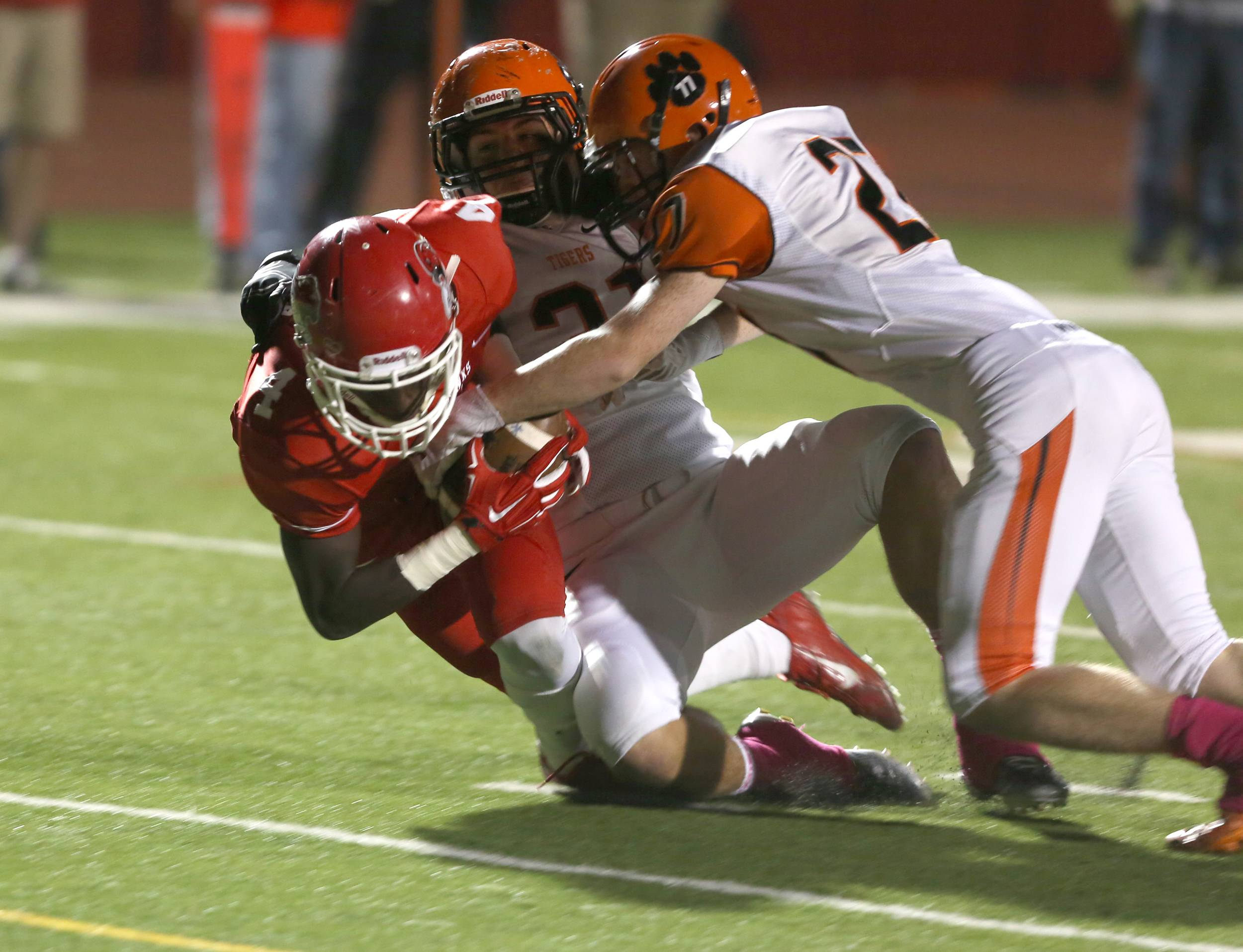 Naperville Central's Emmanuel Rugamba, left, scores a first-quarter touchdown against Wheaton Warrenville South.