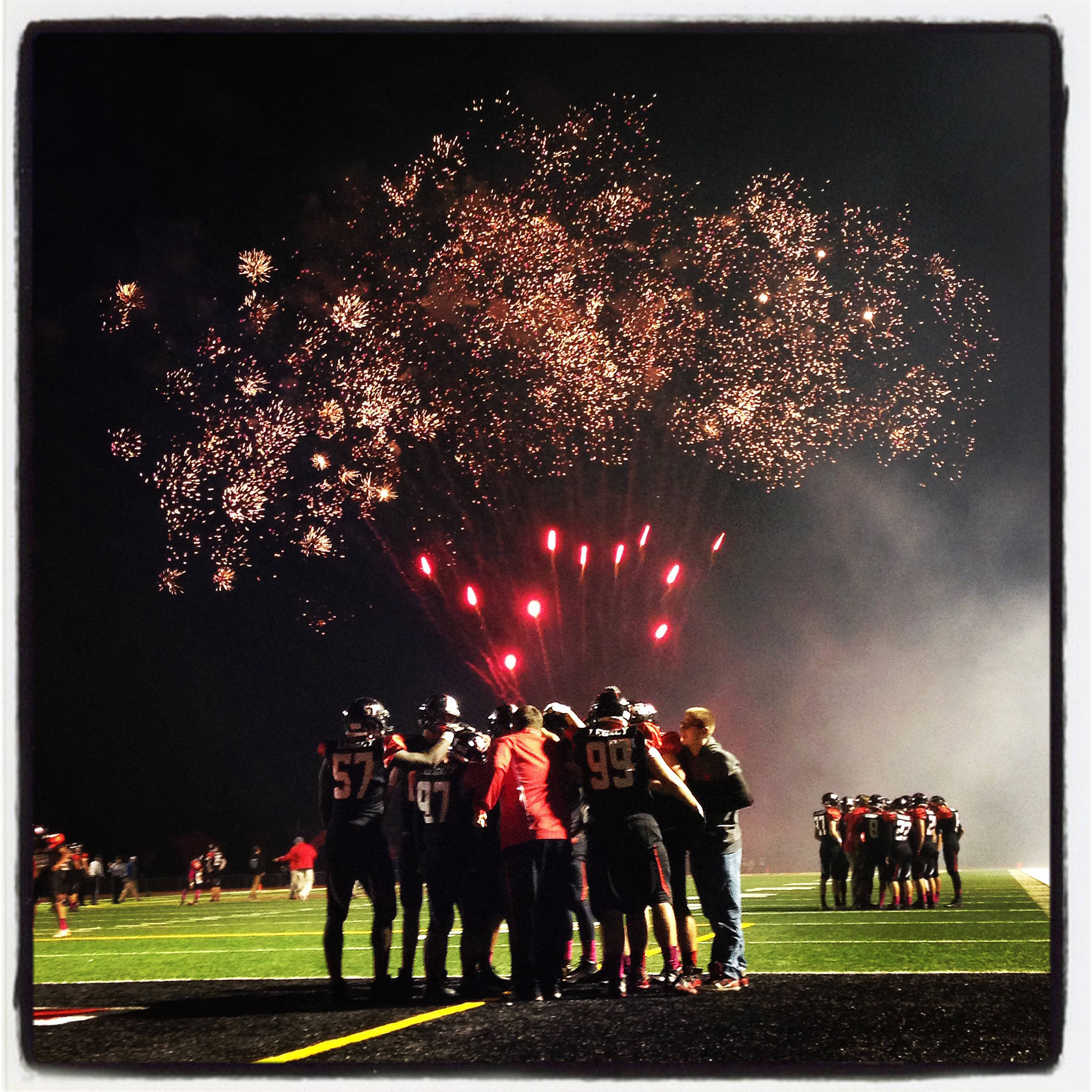 Fireworks entertain fans in the stands while Huntley High School varsity football players huddle up following pre-game warm-up drills.