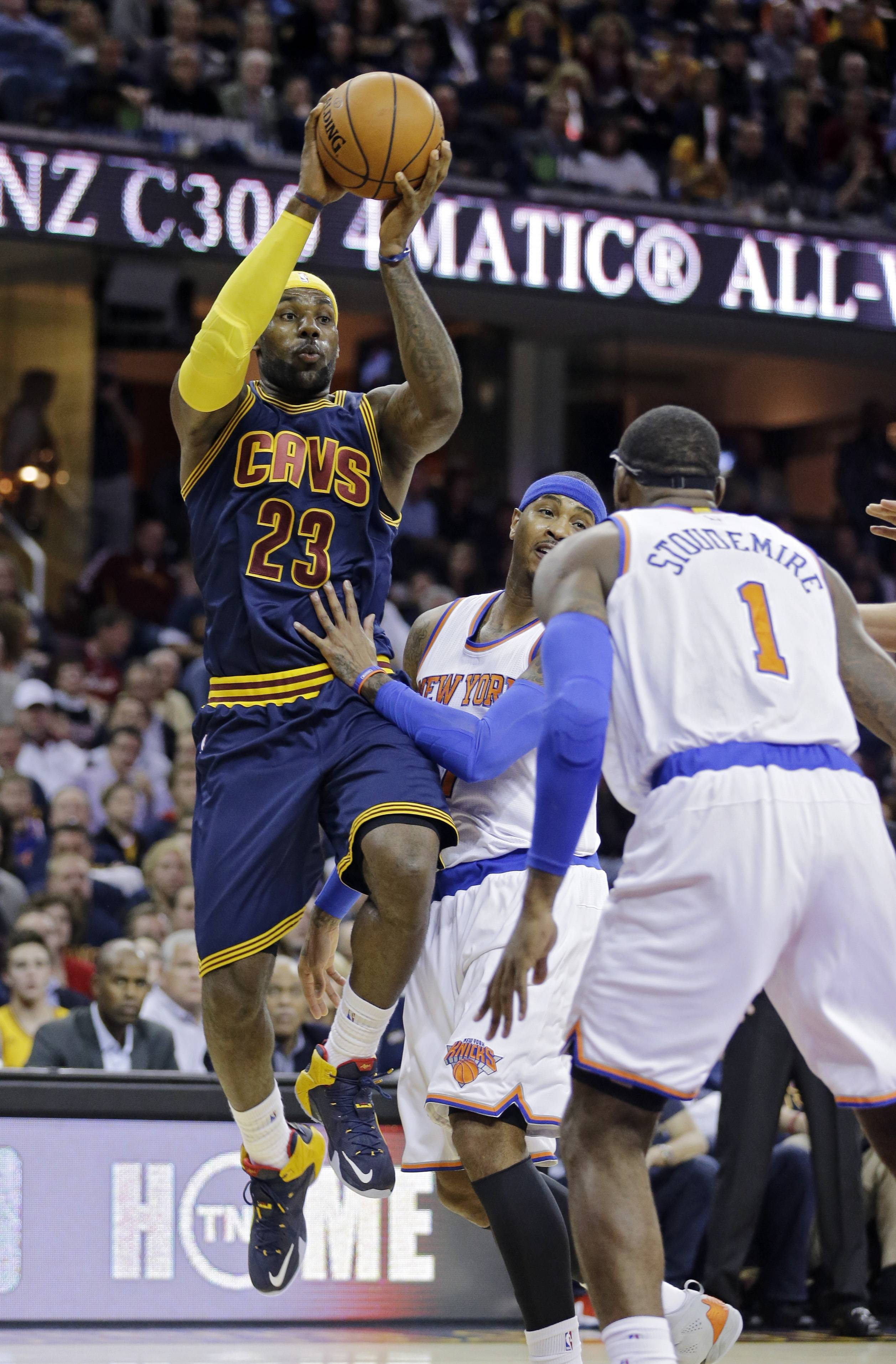 Cleveland Cavaliers' LeBron James (23) looks to pass against New York Knicks' Carmelo Anthony and Amar'e Stoudemire (1) in the first quarter of an NBA basketball game Thursday, Oct. 30, 2014, in Cleveland.