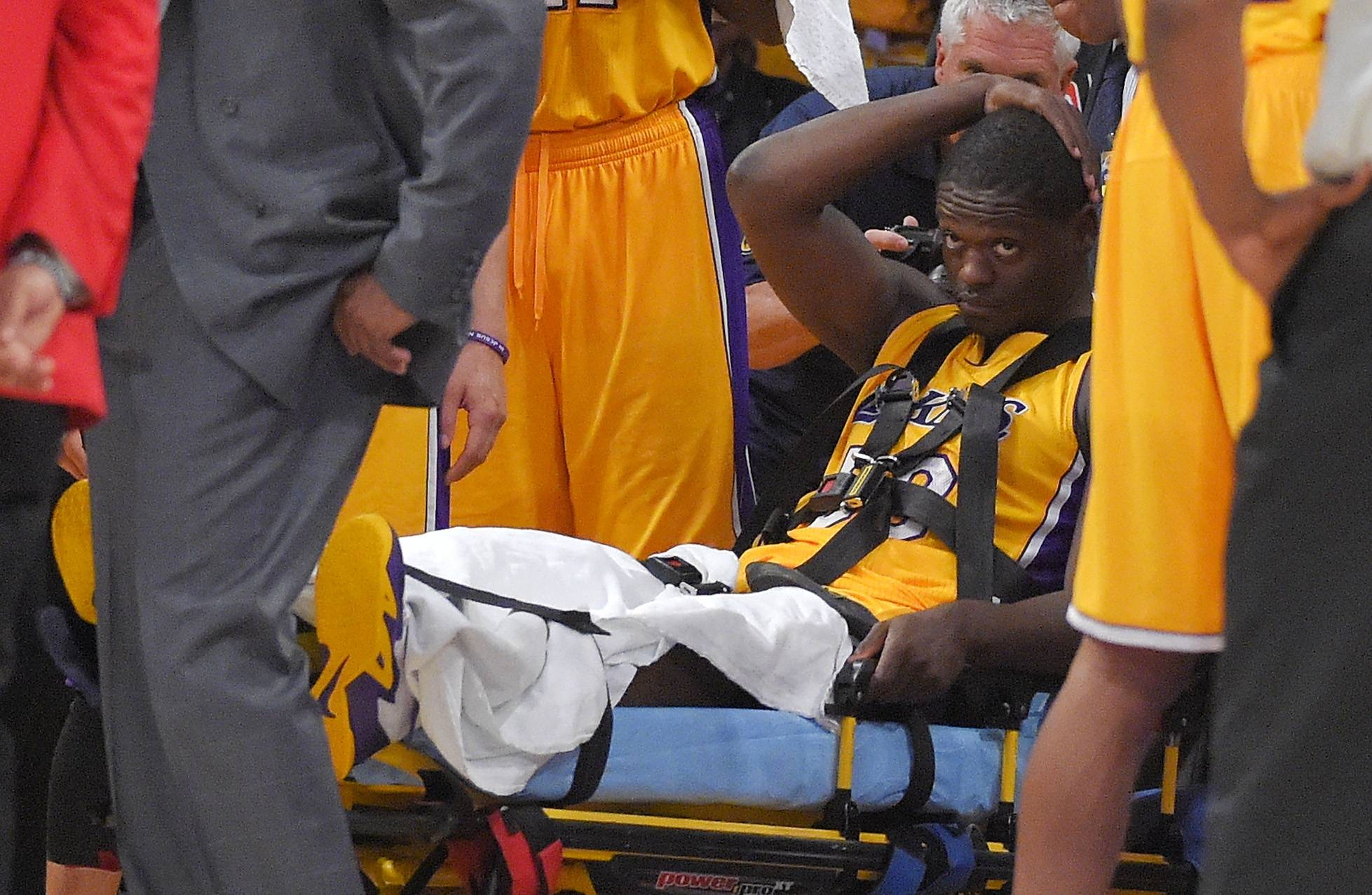 Los Angeles Lakers forward Julius Randle, right, sits on on a stretcher after Randle injured himself on a play during the second half of an NBA basketball game, Tuesday in Los Angeles. Randle is expected to miss the full NBA season.