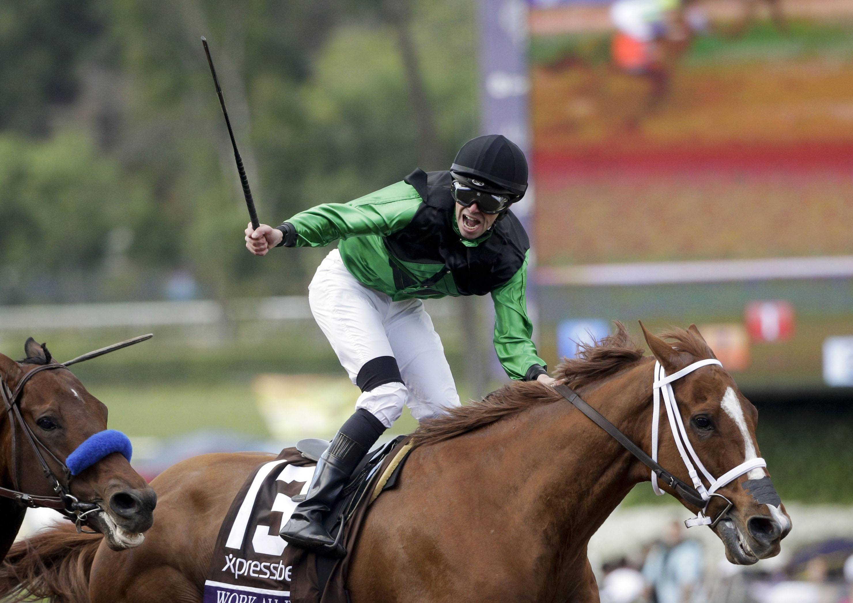 Jockey Florent Geroux celebrates after riding Work All Week to victory in the Breeders' Cup Sprint horse race at Santa Anita Park, Saturday, Nov. 1, 2014, in Arcadia, Calif.