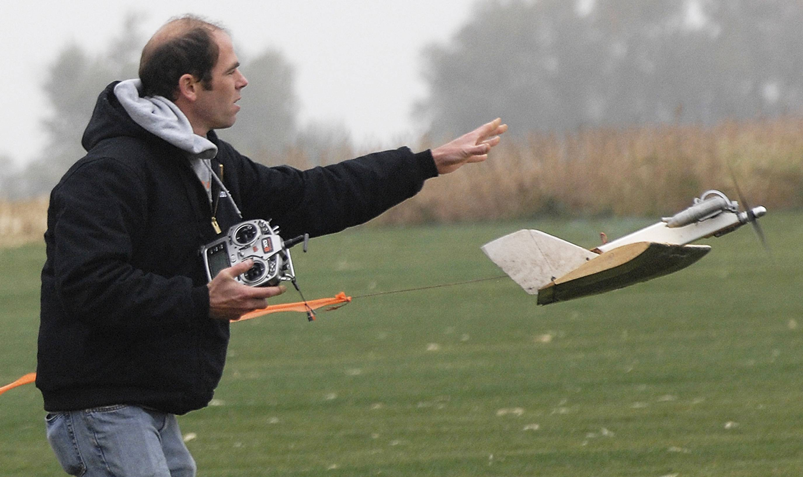 "Dave Hass, of Normal, president of the Sentral Illinois Radio Society, a remote-control airplane club, sends his ""gremlin"" off to combat during the SIRS club's 50th anniversary open house near Funks Grove"