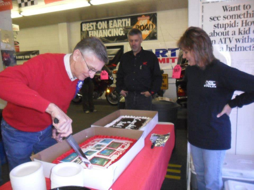 Bob Conley, at left, cuts his retirement cake in 2012 as John Conley and Chris Conley Tracy look on.