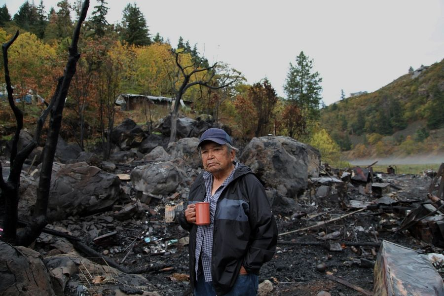 Chief of the Cascade Tribe Johnny Jackson stands in front of the charred remains of his home at the Underwood fishing site at the mouth of the White Salmon River and the Columbia River. Jackson first moved onto the fishing site in the 1960s and built himself a cabin, but it burned along with other structures in September due to a propane leak.