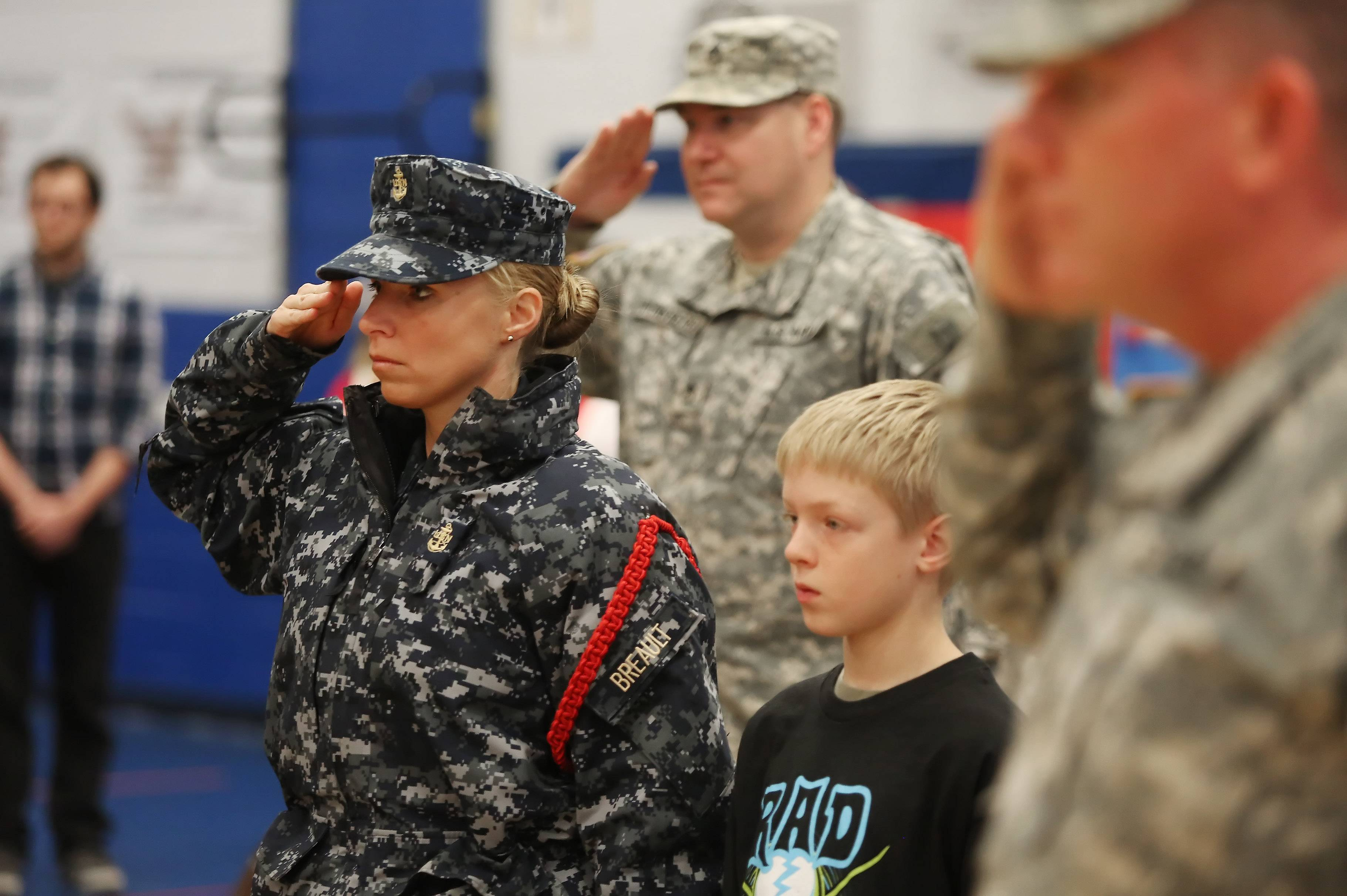 Navy Chief Kristine Breault, left, with her fifth grade son, Jaeger, salute as the flag passes during the Veterans Day assembly Tuesday at Frederick School in Grayslake. The event also featured the Drill Team and Color Guard from Great Lakes Naval Station.