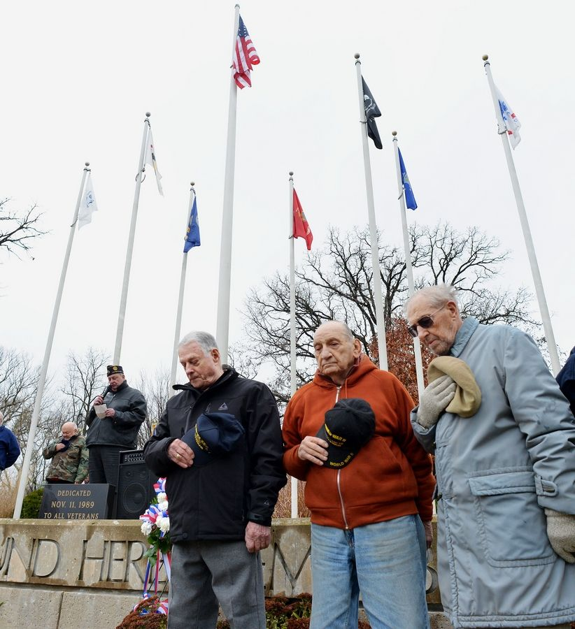 "World War II veterans Joe Marinello and Arnold Massier stand with Korean War veteran Jerry Schlegel as the Naperville Municipal Band plays ""The Star-Spangled Banner"" during the city's Veterans Day ceremony."