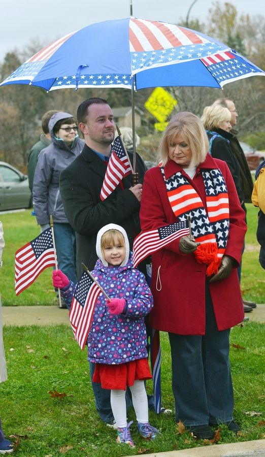 Gabby Budny, front, waves flags along with Matthew and Bernadette Budny at Naperville's Veterans Day ceremony.