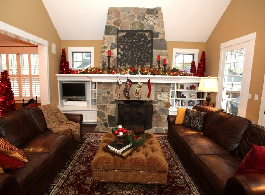 A fireplace decorated for the holidays and comfy couches invite family members and visitors to enjoy the season in the Pierce home.