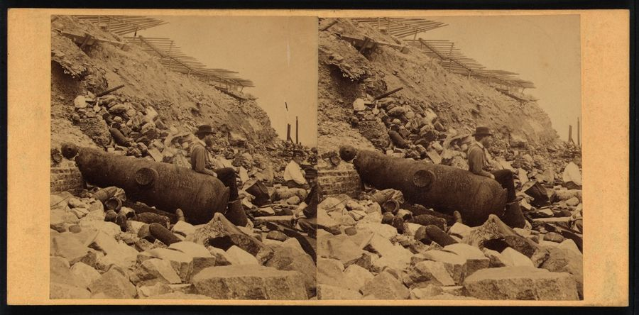Two men sit on rocks amidst the debris of exterior of Fort Sumter, S.C., as one man leans on a cannon.