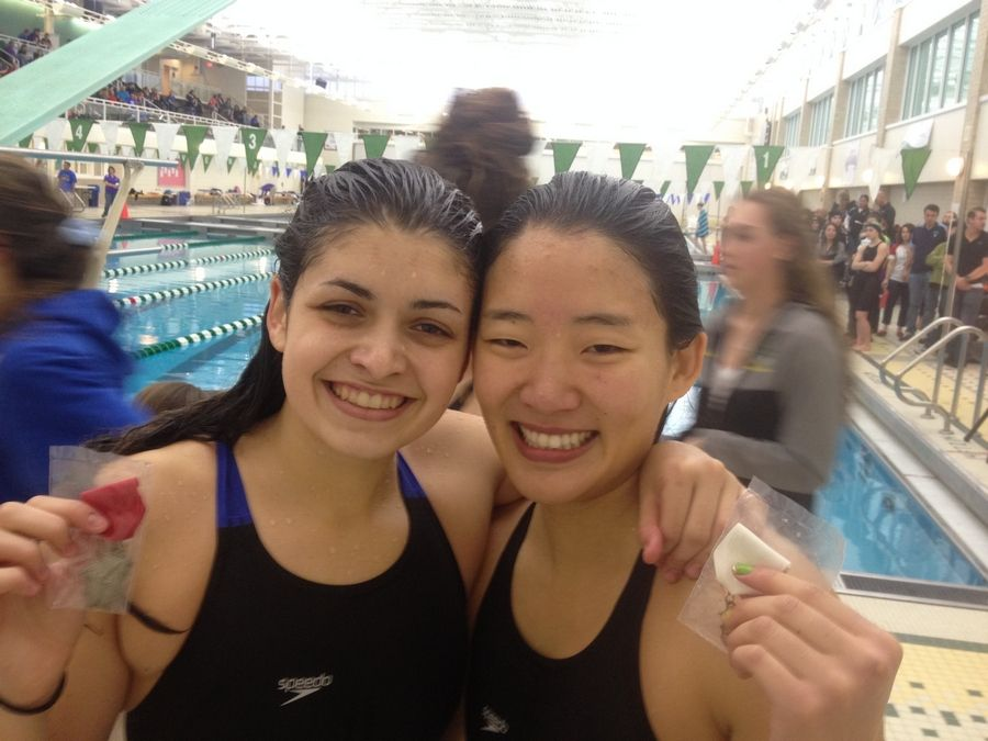 Fremd's Grace Grzybek, left, and Saki Takumiya share a moment behind the starting blocks after their state-qualifying performances in the 100 backstroke at the Stevenson sectional.
