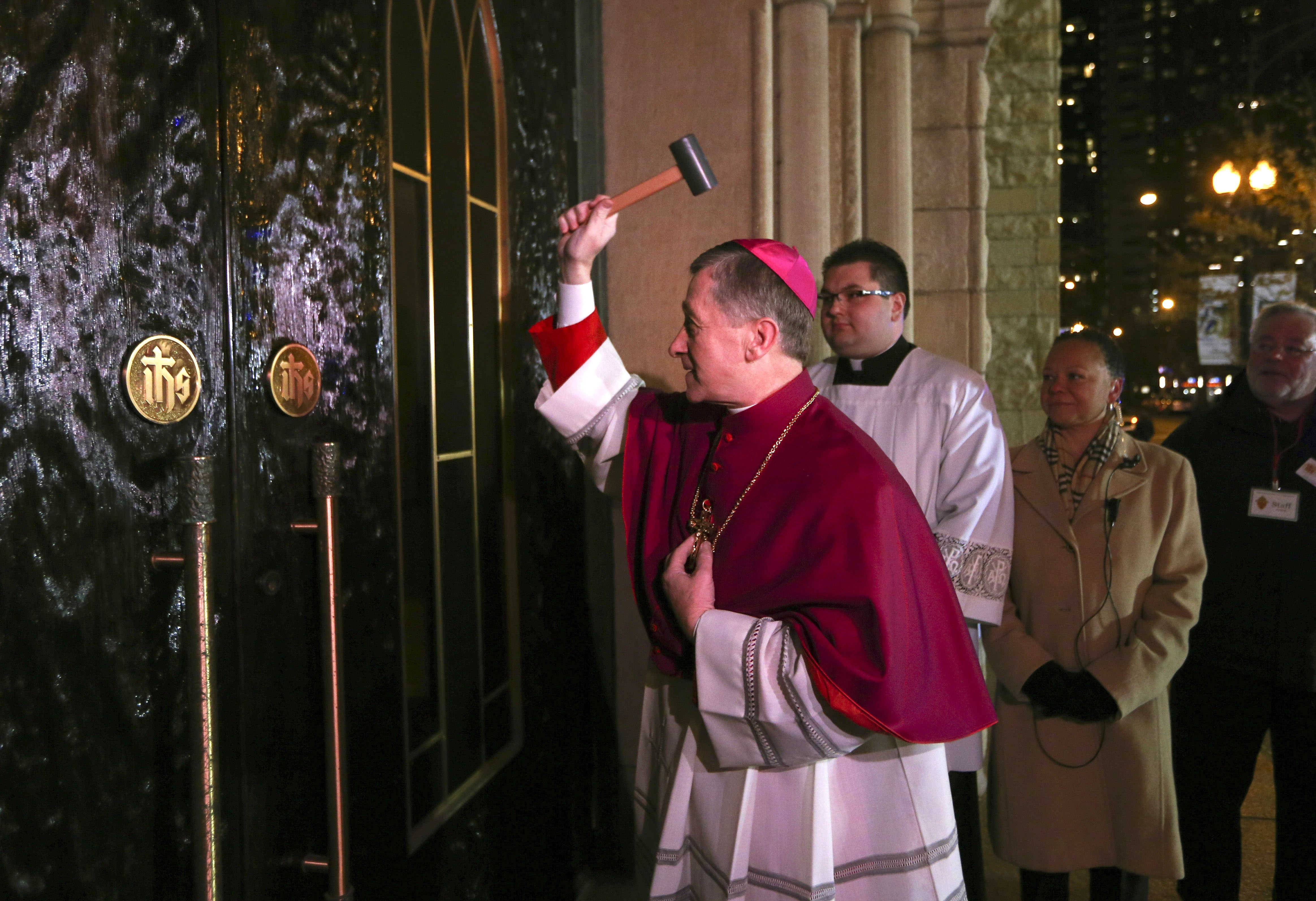 Incoming Archbishop Blase Cupich knock on the front doors before the Rite of Reception ceremony, at Holy Name Cathedral at 735 N. State St., in Chicago, on Monday, Nov. 17, 2014.