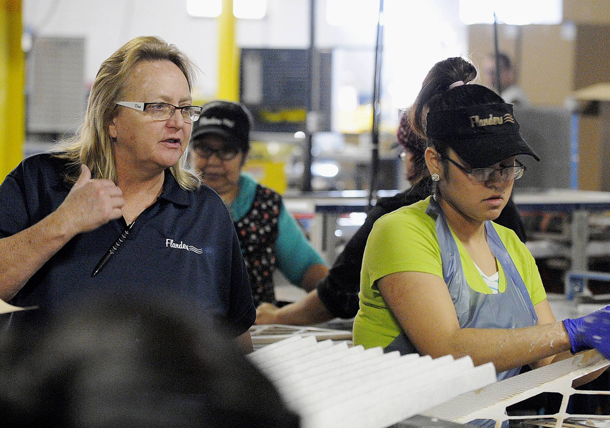 Donna Osteen, left, general manager of Flanders Precisionaire of Illinois, in Momence, watches over workers in the facility. Osteen is in charge of a workforce of 400 in a plant that produces $32 million in air filters each year.