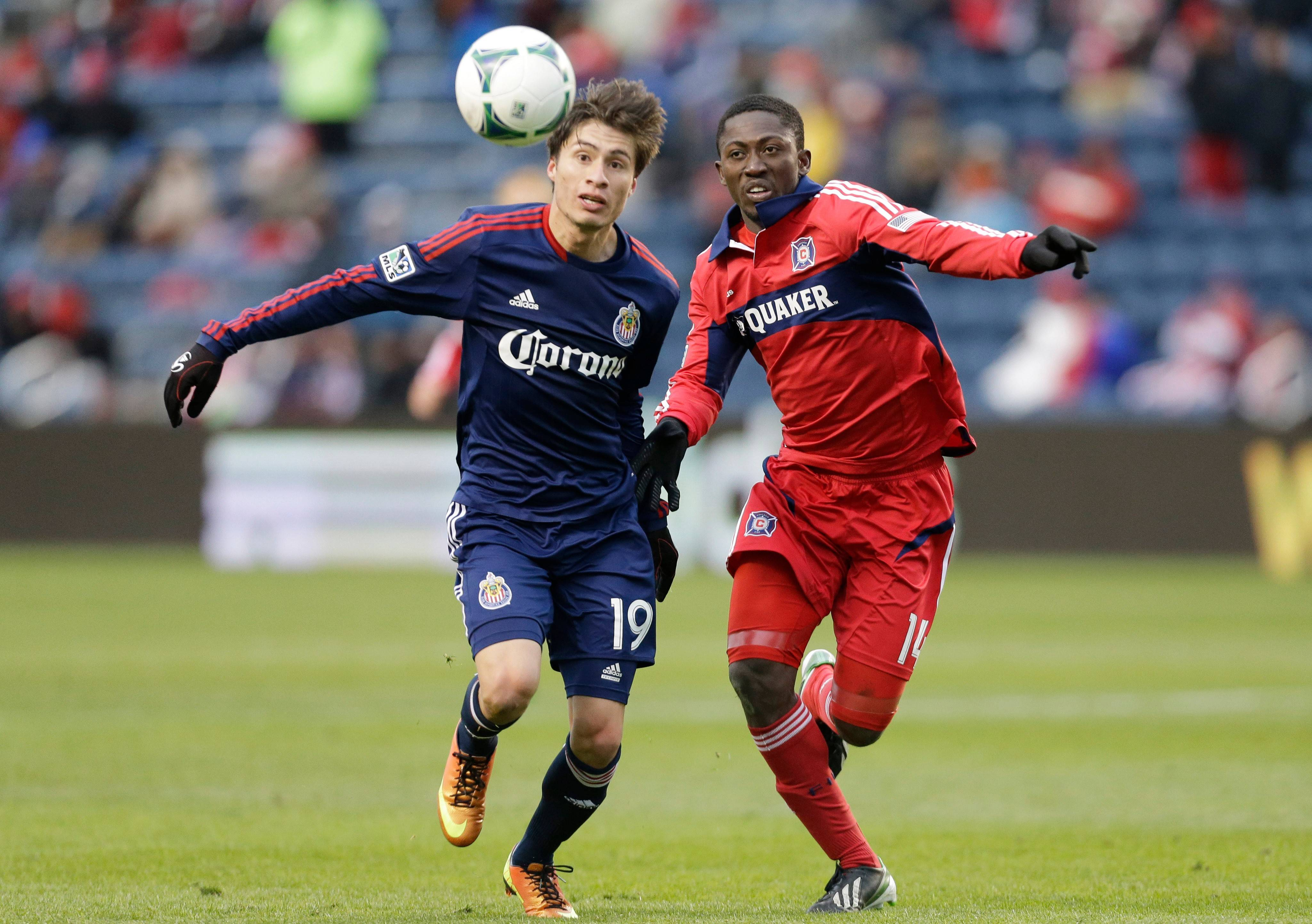 Chivas USA forward Jorge Villafana, left, and Chicago Fire forward Patrick Nyarko, right, chase the ball during the second half of an MLS soccer match in Bridgeview, Ill., Sunday, March 24, 2013. Chivas USA won 4-1. (AP Photo/Nam Y. Huh)