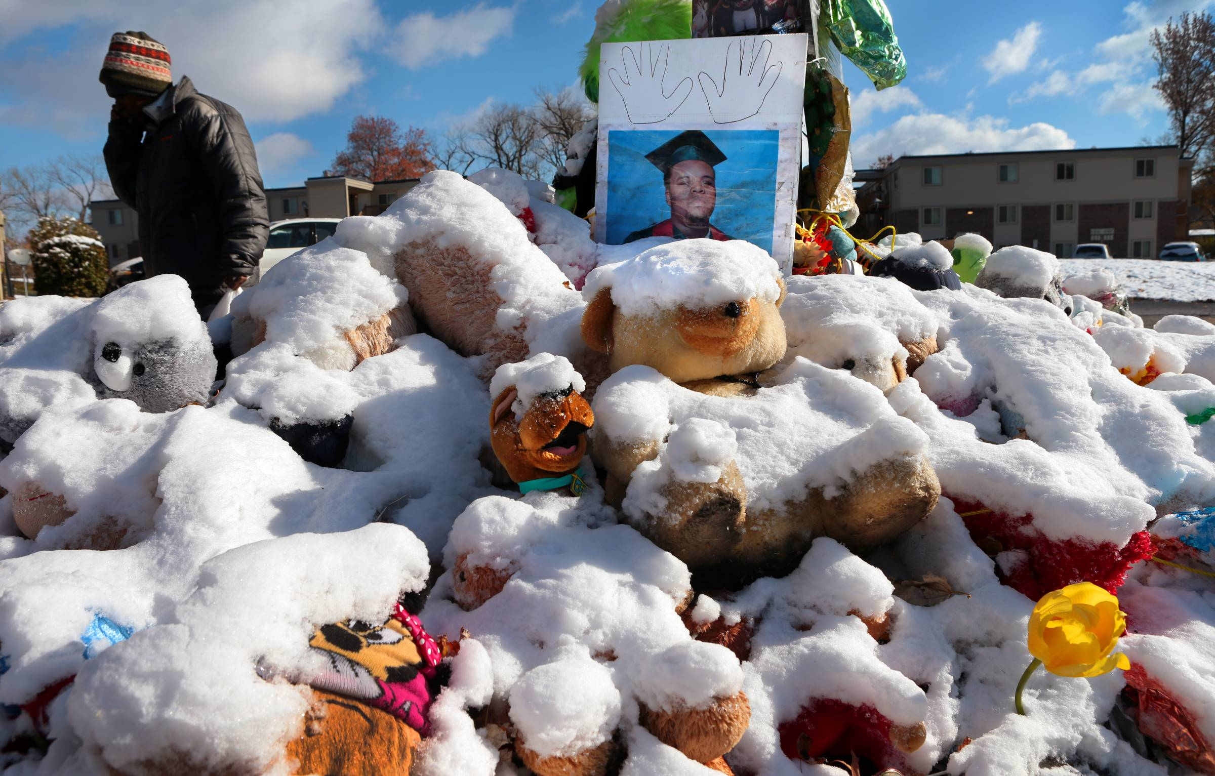 A high school graduation photo of Michael Brown rests on top of a snow-covered memorial Monday, more than three months after the black teen was shot and killed nearby by a white policeman in Ferguson, Mo. The shooting sparked weeks of violent protests and  Missouri Governor Jay Nixon declaring a state of emergency Monday as a grand jury deliberated on whether to charge Ferguson police officer Darren Wilson in the death.