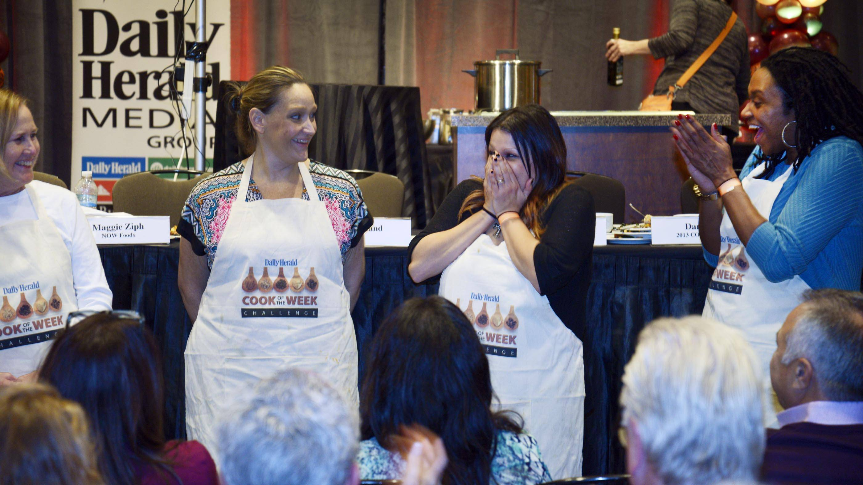 Jamie Andrade, of Elk Grove Village, reacts Monday as she is named the Daily Herald 2014 Cook of the Year after a cook-off earlier this month at the Hyatt Regency Schaumburg. Other contestants are, Molly Sutton, of Arlington Heights, left, Emily Geddes, of Geneva, and Juanita Harrell, of Wheaton, right.